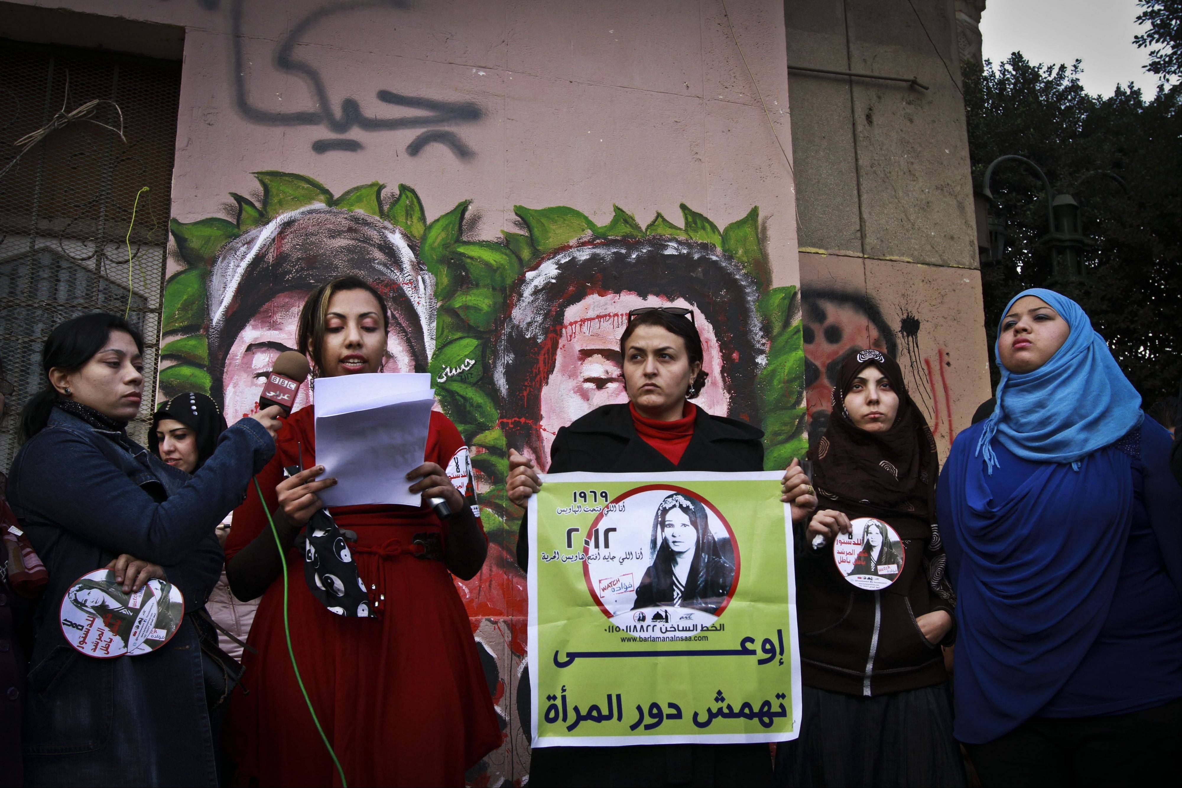 An Egyptian woman holds a banner with Arabic that reads, �do no marginalize the role of a woman,� Tuesday during a demonstration in Tahrir Square, Cairo, Egypt. Women cut their hair to protest against the Islamist-oriented constitution on Tuesday.