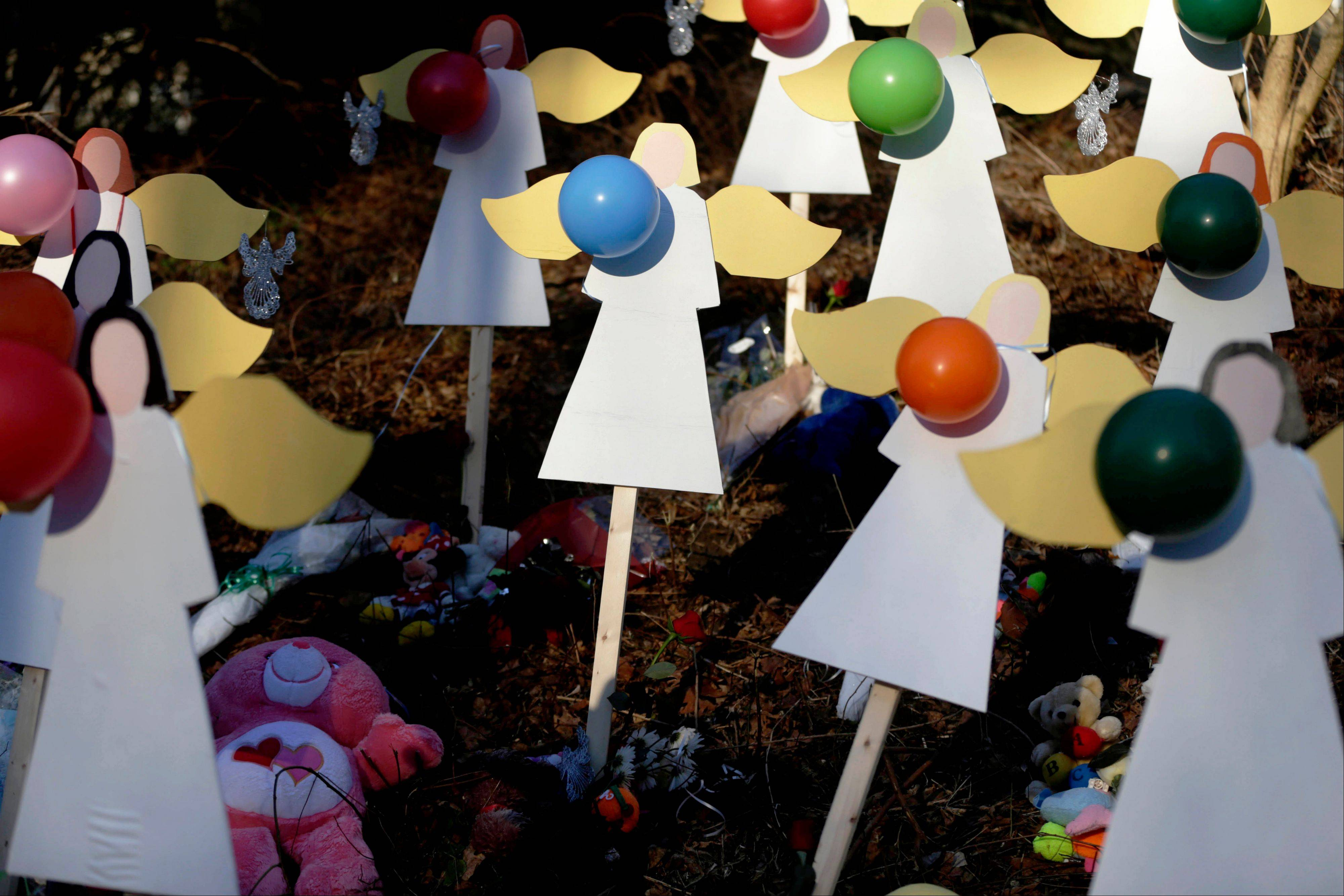 Wooden angels are displayed as part of memorial to shooting victims in Newtown, Conn., Thursday, Dec. 20, 2012. Aanxious parents are buying armored backpacks for children and firearms enthusiasts stocking up on semiautomatic rifles in anticipation of tighter gun control measures.
