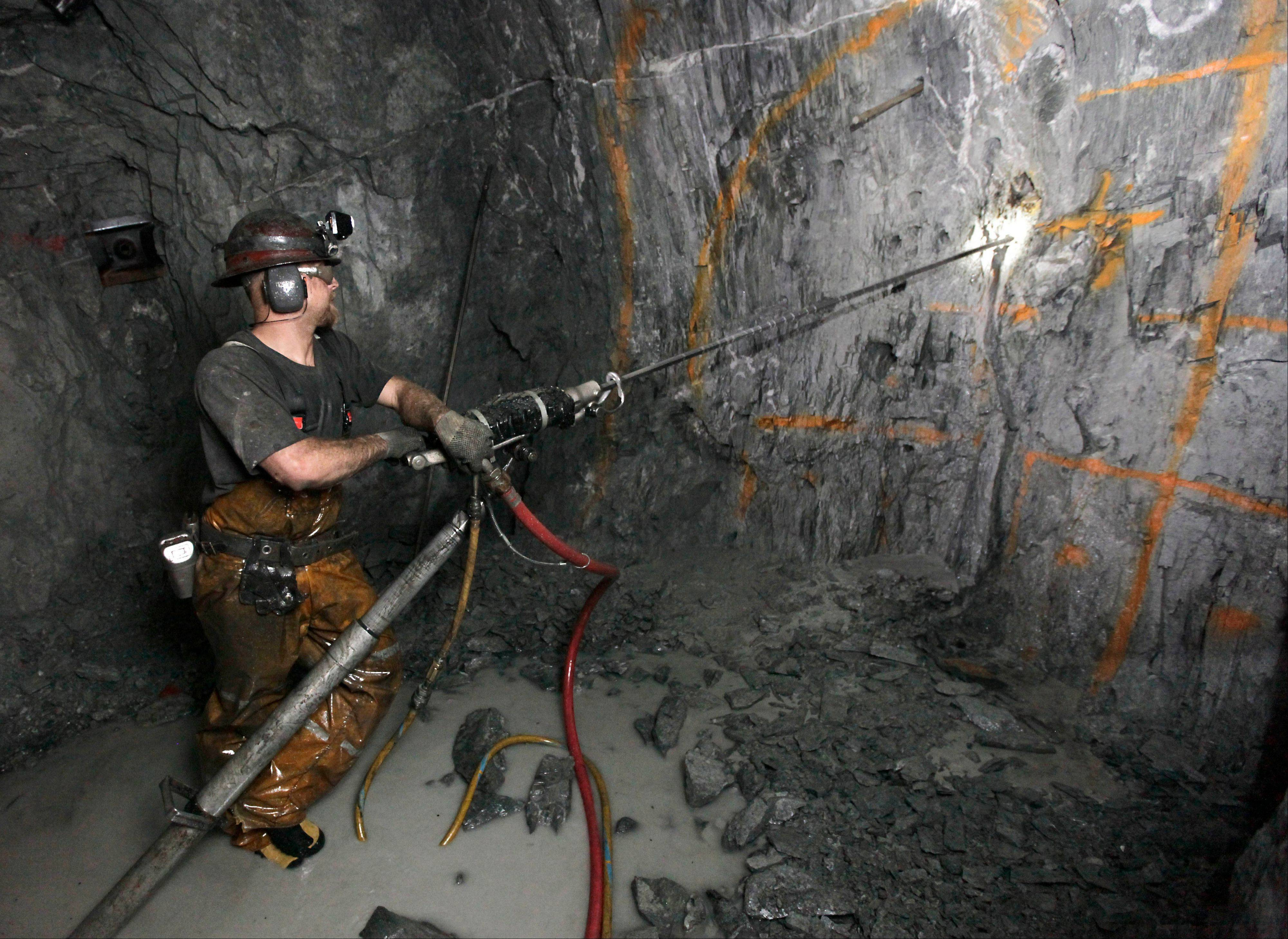 Miner Keith Emerald uses a pneumatic drill to drill holes that will be packed with explosives to blast into the sold rock wall at the Sutter Gold Mining Co's mines near in Sutter Creek, Calif.