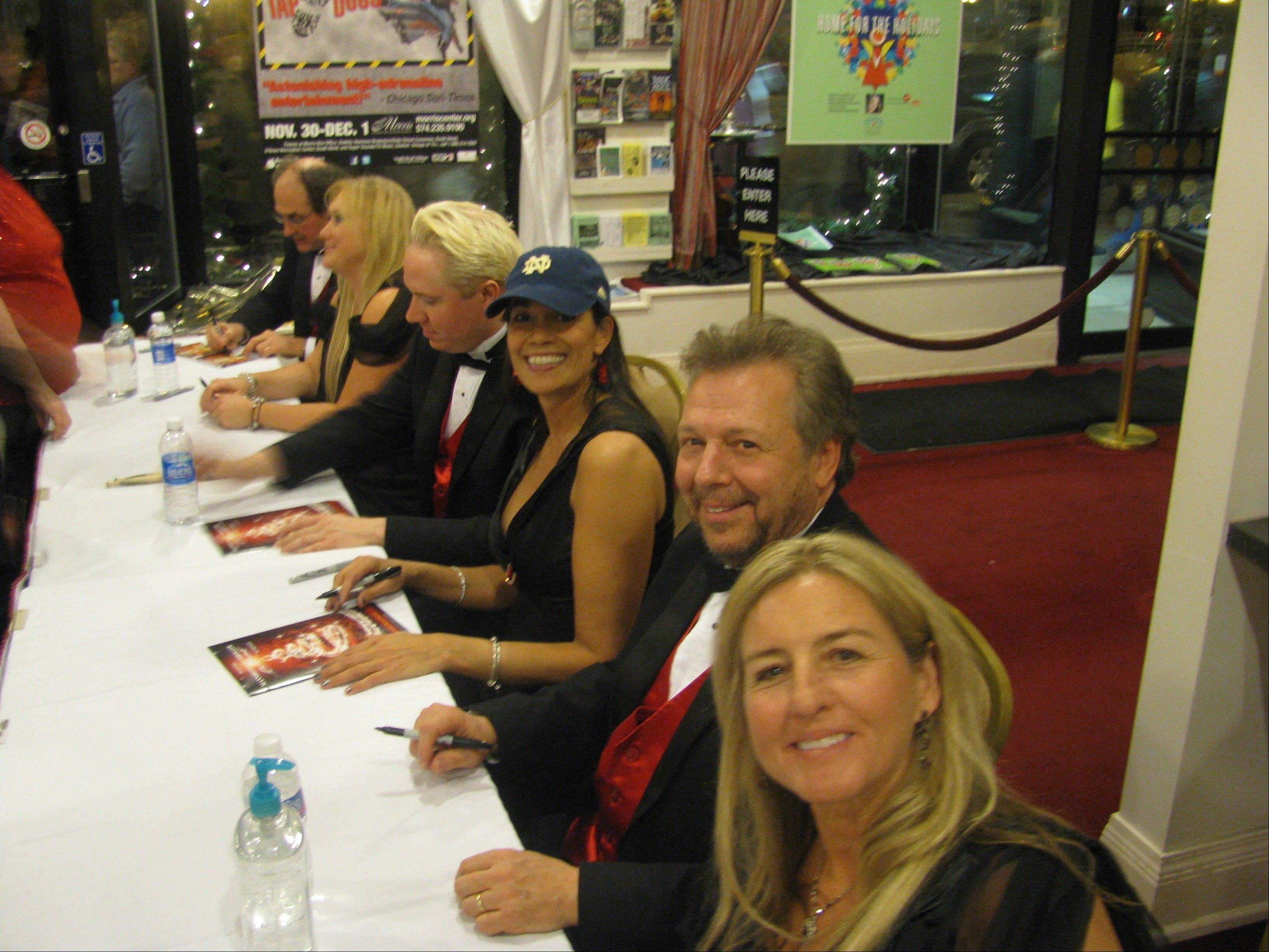 Violinist Becky Kia, third from right, signs autographs following a performance with Mannheim Steamroller.