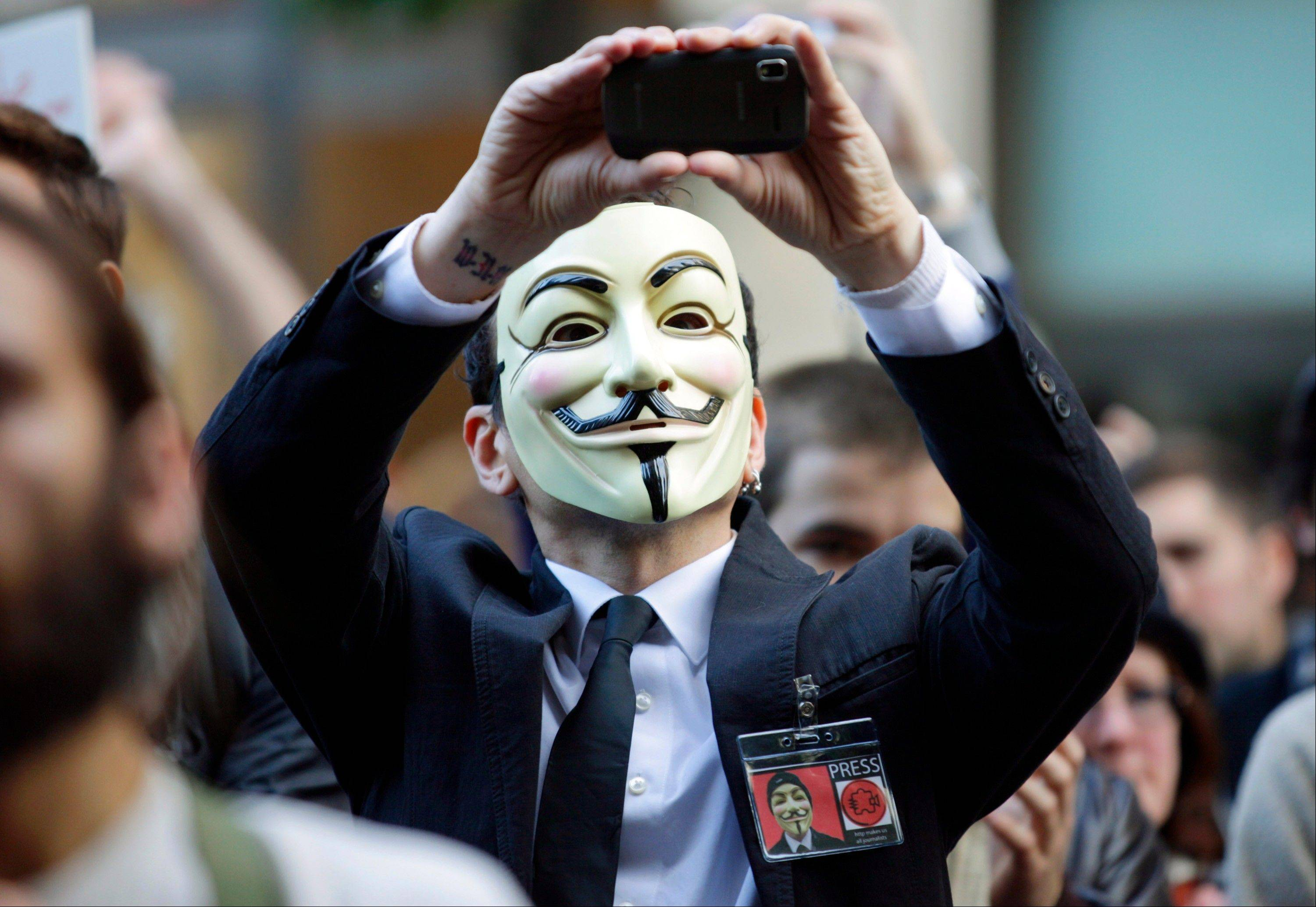 "A protester with the ""Occupy Seattle"" movement wears a Guy Fawkes mask and takes a photo with a mobile phone as he demonstrates, in downtown Seattle. Television audiences across China watched an anarchist antihero rebel against a totalitarian government and persuade the people to rule themselves."