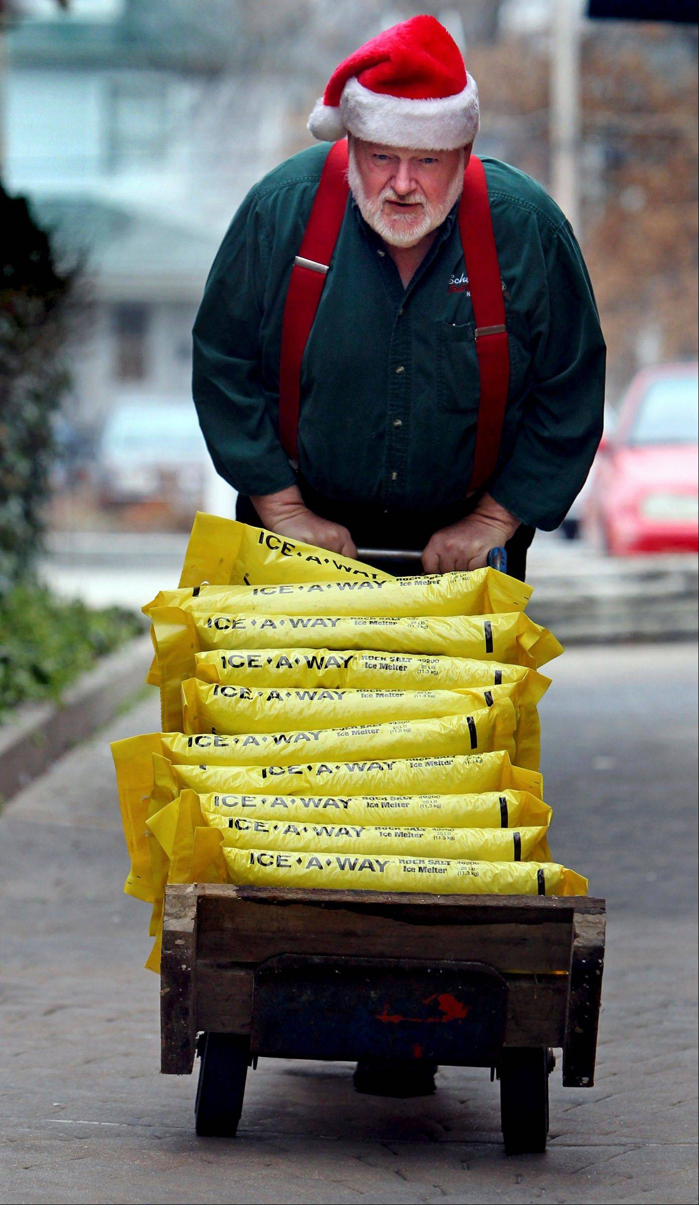 Roger McCreight, a hardware store employee, brings up the remaining bags of rock salt from the basement inventory to stock in the store for customers Monday, Dec. 24, 2012, in Maplewood, Mo., in anticipation of wintry weather.