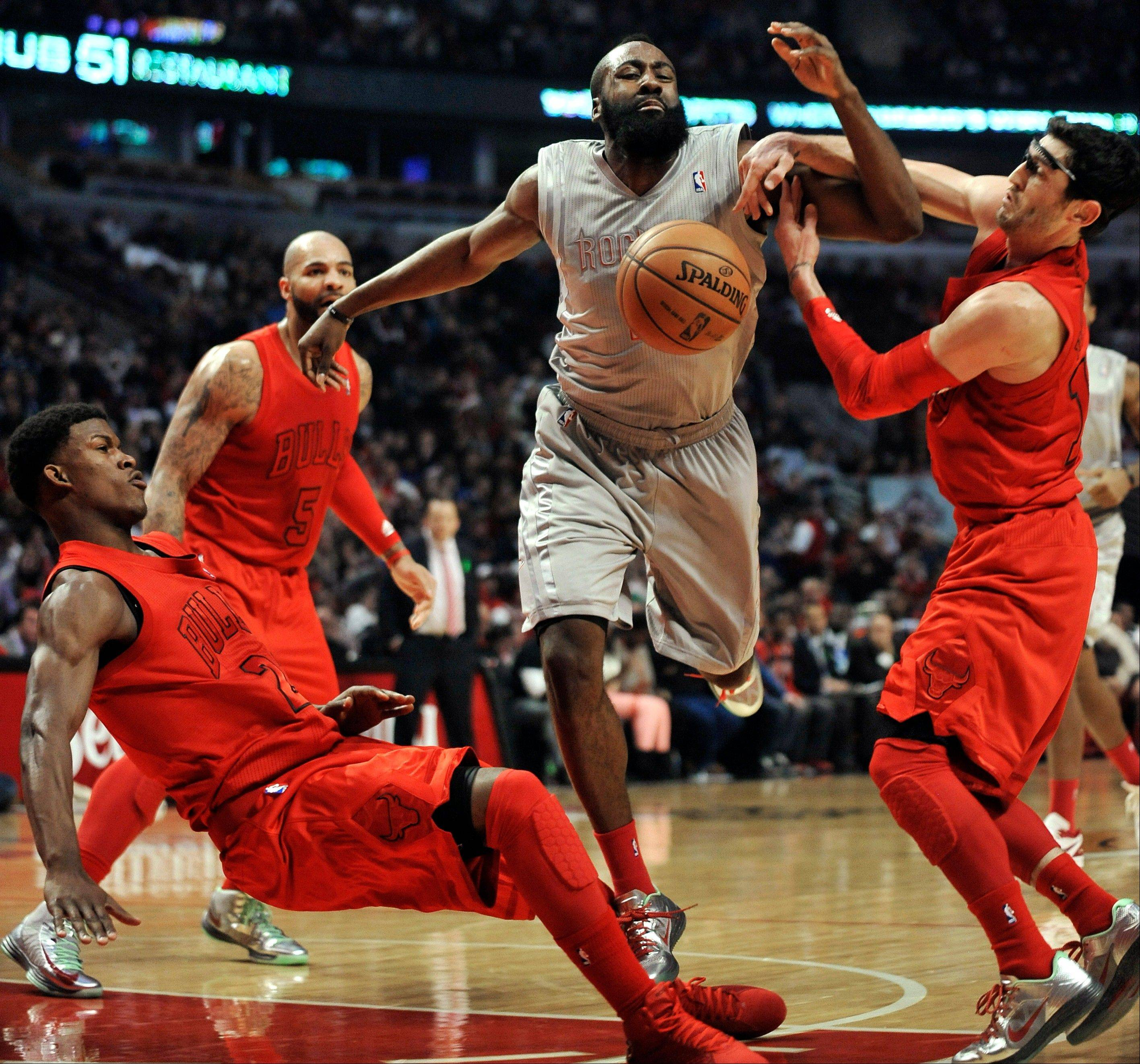 Houston Rockets' James Harden, center, battles Chicago Bulls' Kirk Hinrich, right, and Jimmy Butler, left, for a loose ball during the first quarter of an NBA basketball game in Chicago, Tuesday, Dec. 25, 2012.