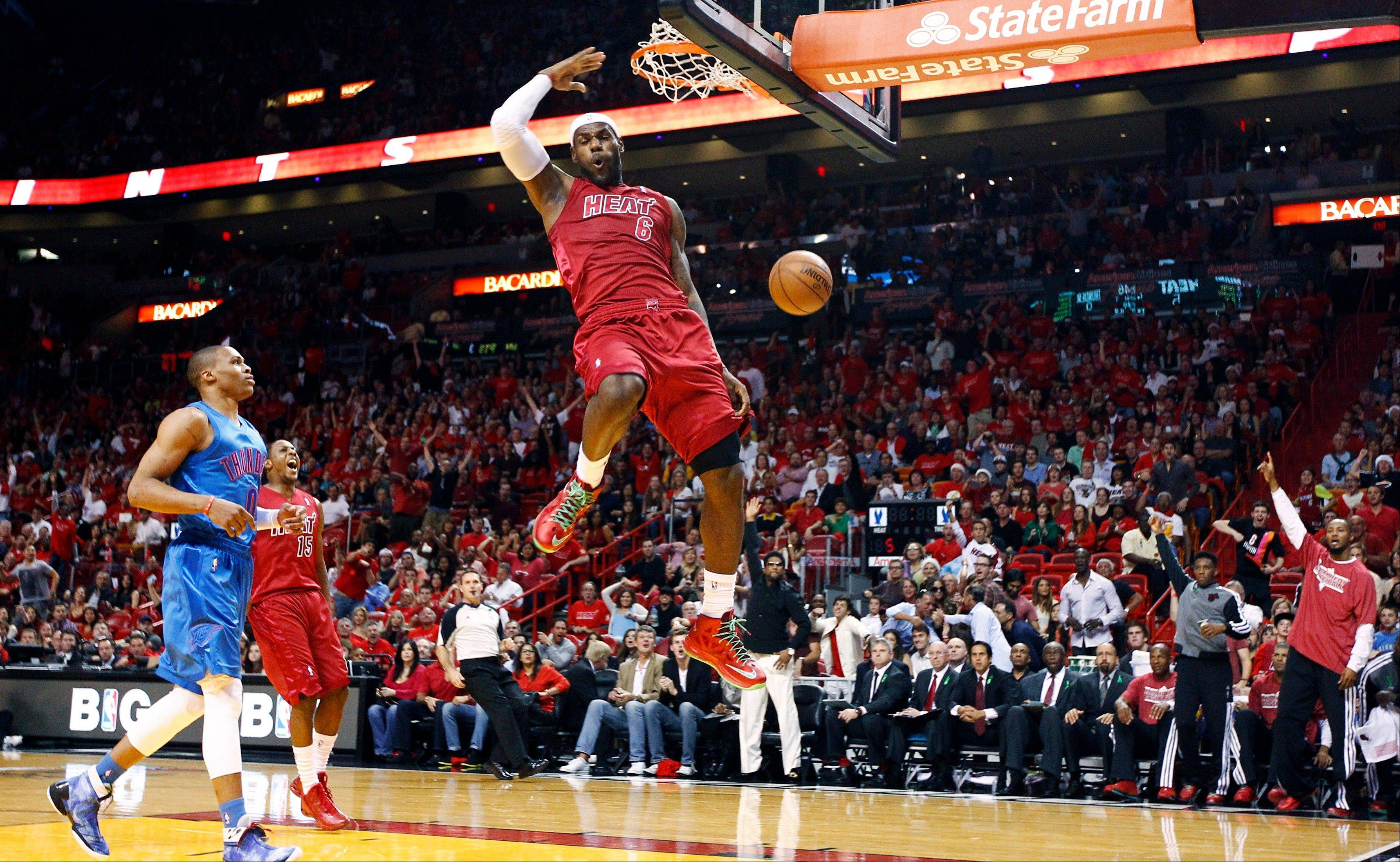 Miami Heat forward LeBron James dunks as Oklahoma City Thunder's Russell Westbrook (0) and Heat's Mario Chalmers watch Tuesday during the first half in Miami.