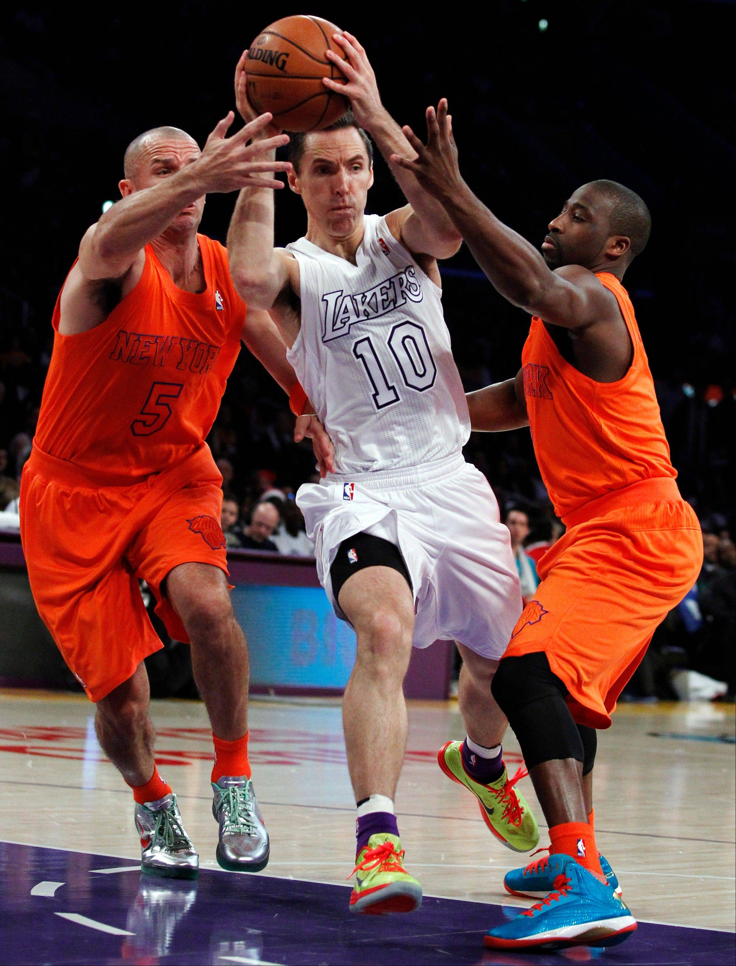 Los Angeles Lakers guard Steve Nash drives between New York Knicks guards Jason Kidd (5) and Raymond Felton (2) Tuesday during the first half in Los Angeles.