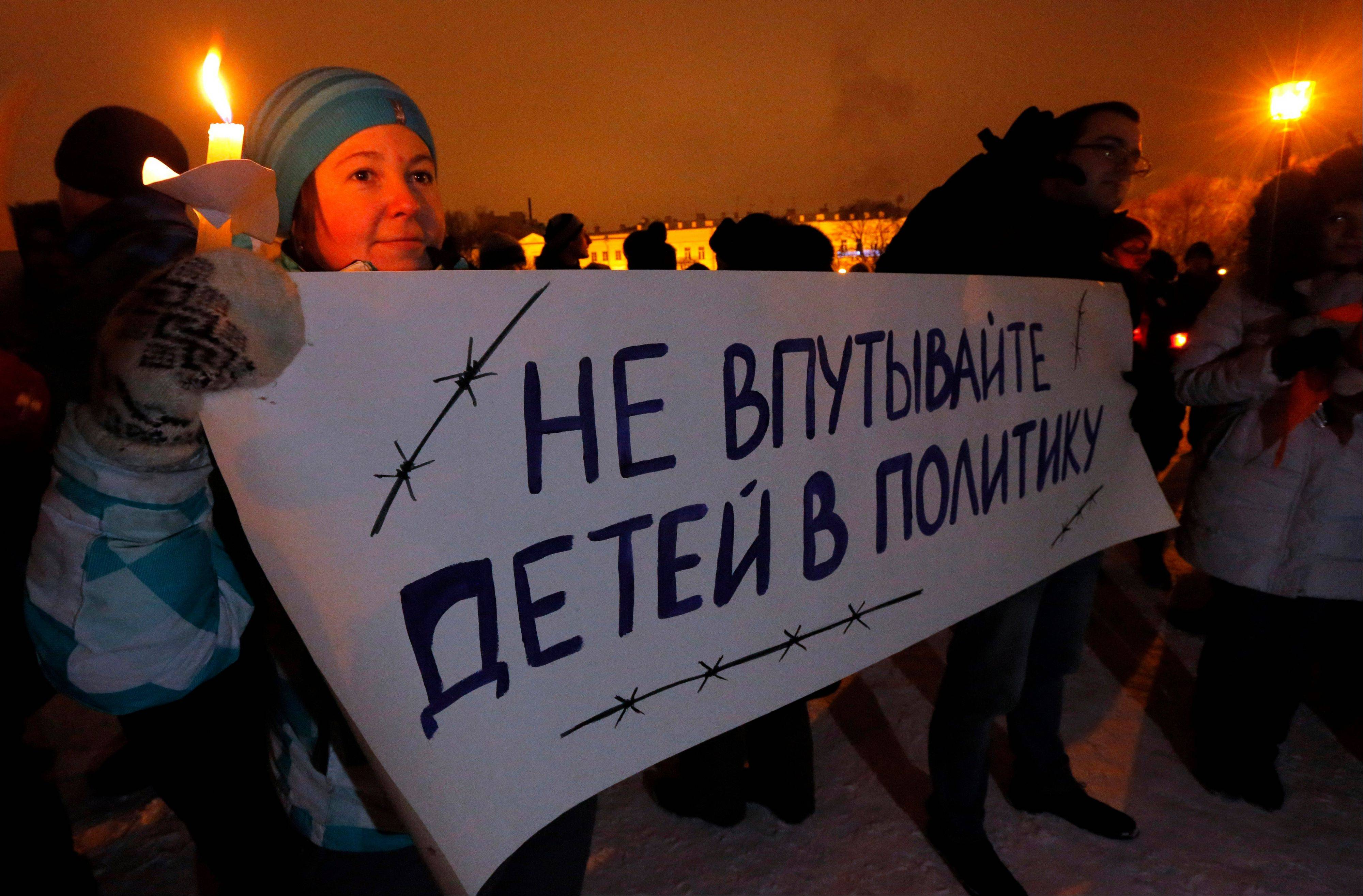 Opposition activists hold a poster reading �Do not involve children in politics� during a protest against a bill banning U.S. adoptions of Russian children in St. Petersburg, Russia, Wednesday.