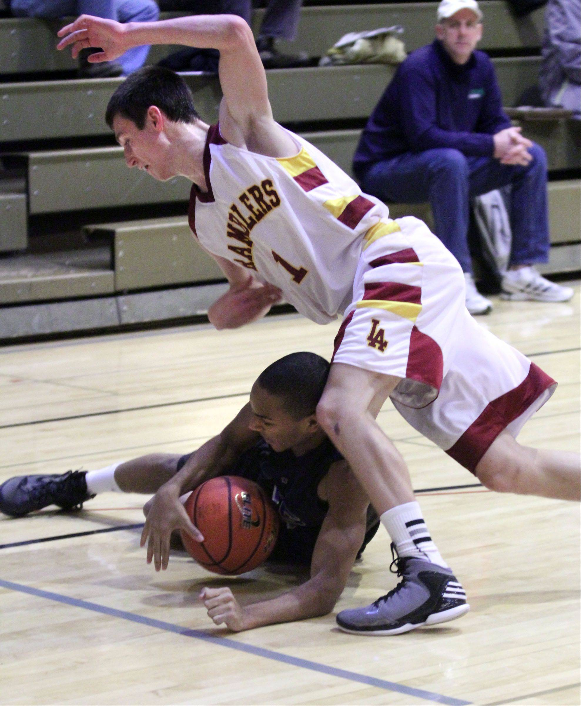 Loyola defender Kevin Kucera falls over Wheeling�s Nate Laude after a battle for a loose ball in Wheeling on Wednesday.