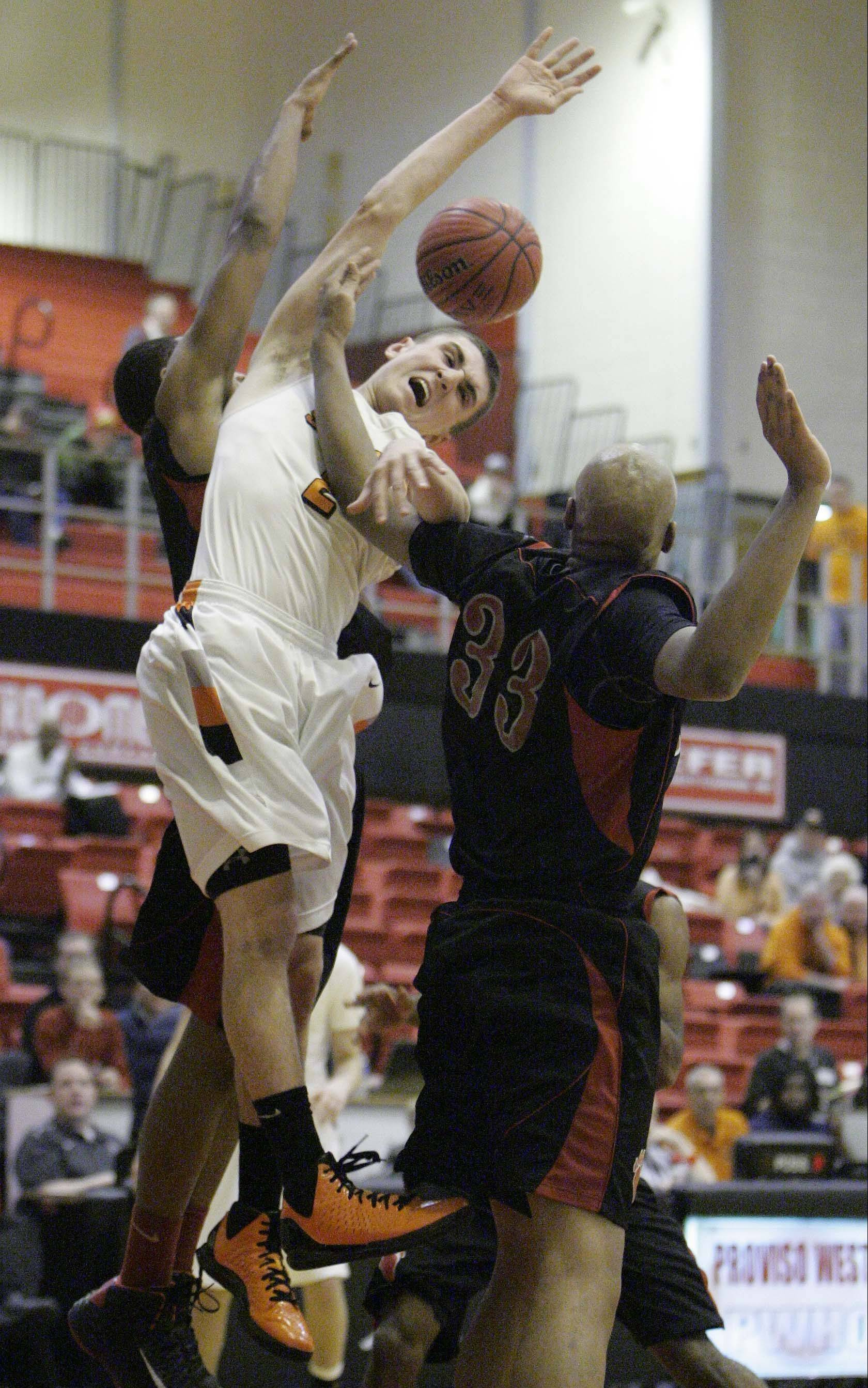St. Charles East�s Dom Adduci is fouled by Von Steuben�s Malachi Matias, 33, Wednesday at the Proviso West Holiday Tournament in Hillside.