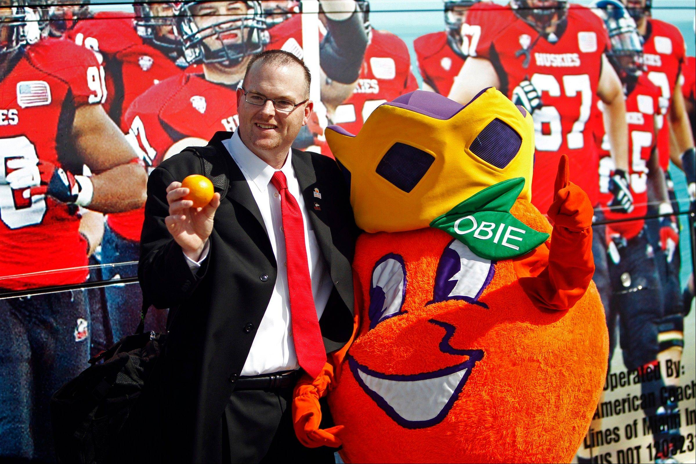 Northern Illinois head coach Rod Carey poses with Obie, the Orange Bowl mascot, Wednesday as the team arrives at Miami International Airport in Miami. Northern Illinois is scheduled to play Florida State in the Orange Bowl on Tuesday.