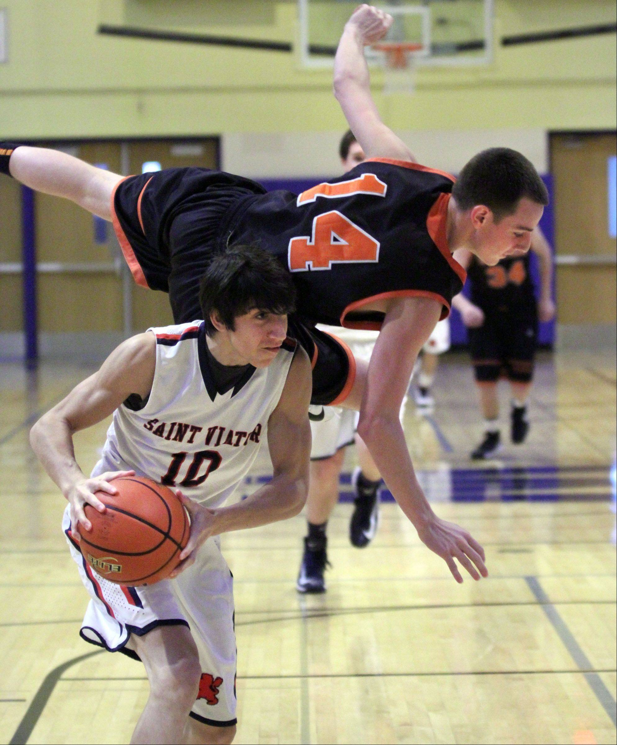 While trying to block a shot Libertyville defender, Drew Cayce falls over the back of St. Viator�s Robert Grant at the 35th annual Hardwood Classic in Wheeling on Wednesday.
