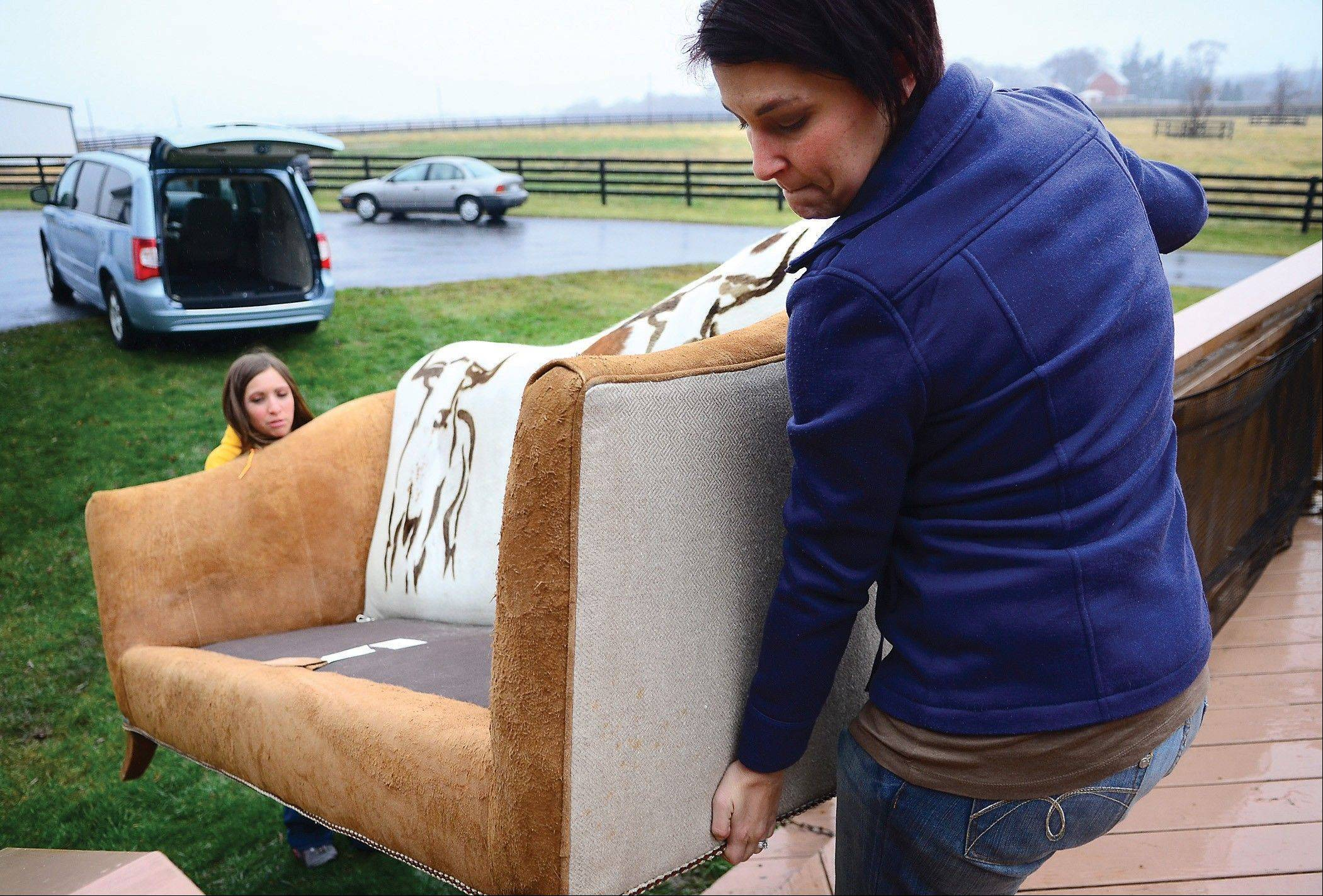 Associated Press  Anneliese Benesh, left, and Erin Wustrack of Omrol, Wis. lug Benesh's custom cowhide couch to their van in Dixon/