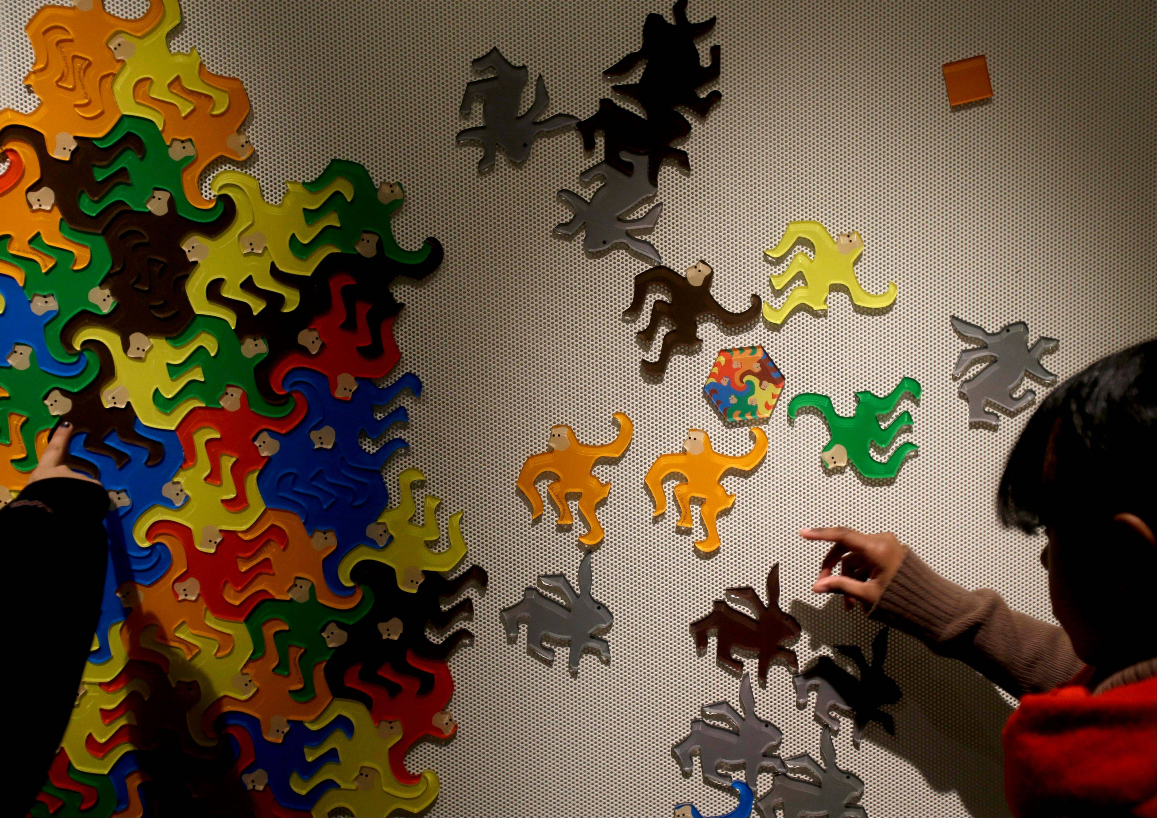 "Students play with interlocking shapes at the museum's Tessellation Station at the National Museum of Mathematics. The museum's 40 exhibits include a ""wall of fire"" made up of laser lights that teaches kids about geometry and a square-wheeled tricycle that still manages to produce a smooth ride thanks to a wavy track."