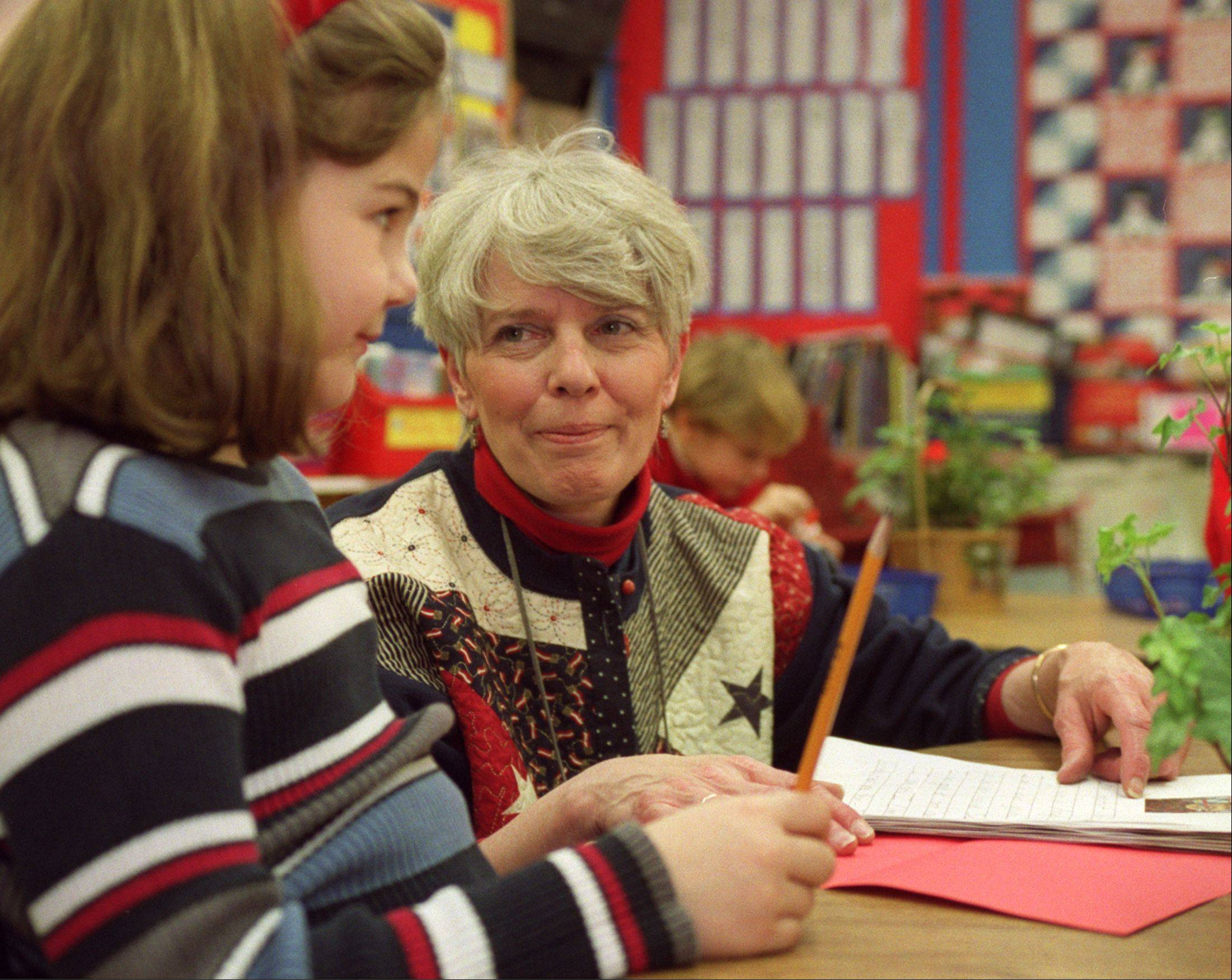 Teacher Mary Bencini works with a student on a Valentine's Day letter during class on Friday at Western Avenue Elementary School in Geneva.