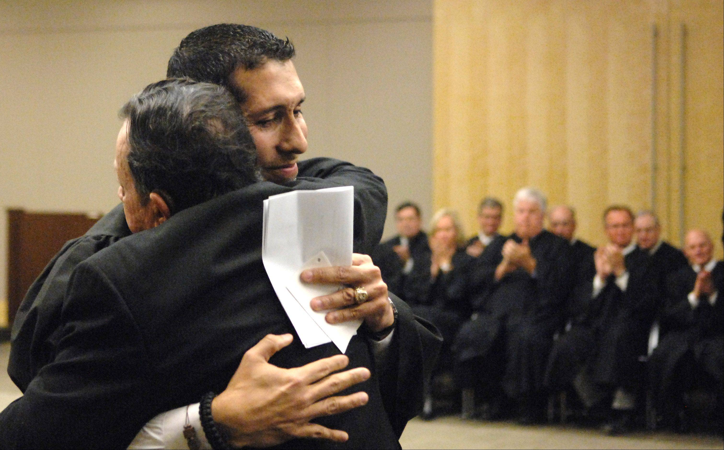 Rene Cruz hugs his father Florencio after being sworn in as Kane County's first Hispanic judge at a ceremony at the Kane County branch court in Geneva.