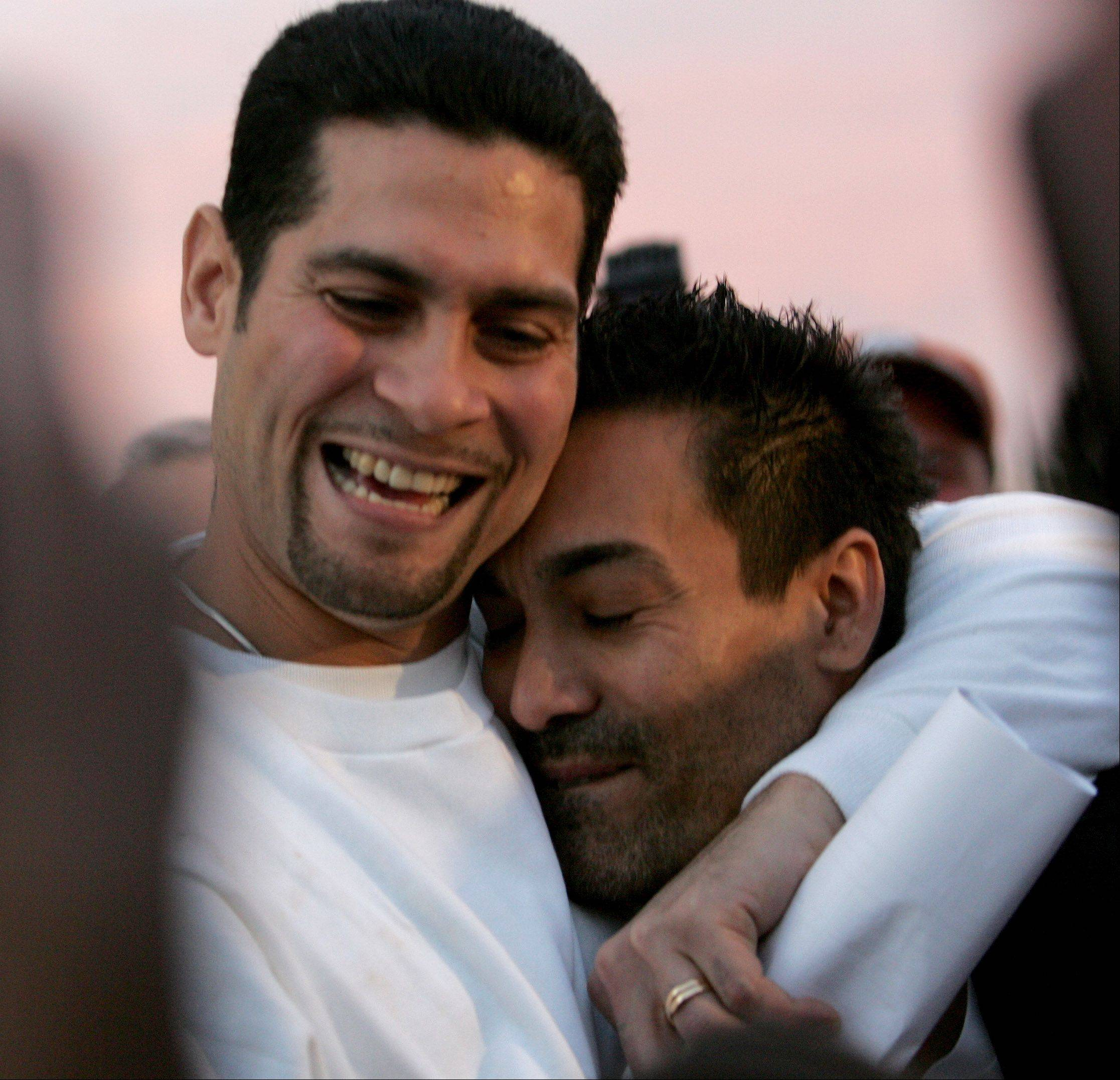 Juan Rivera gives a hug to Miguel Diaz, right, after he is released from Stateville State Prison.