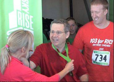 Senator Mark Kirk smiles and accepts his medal as he comes out of the stairwell on the 103rd floor of the Willis Tower Sunday during a benefit climb for the Rehabilitation Institute of Chicago. Kirk has been recovering from a stroke and working with RIC Physical Therapist Michael Klonowski, right.