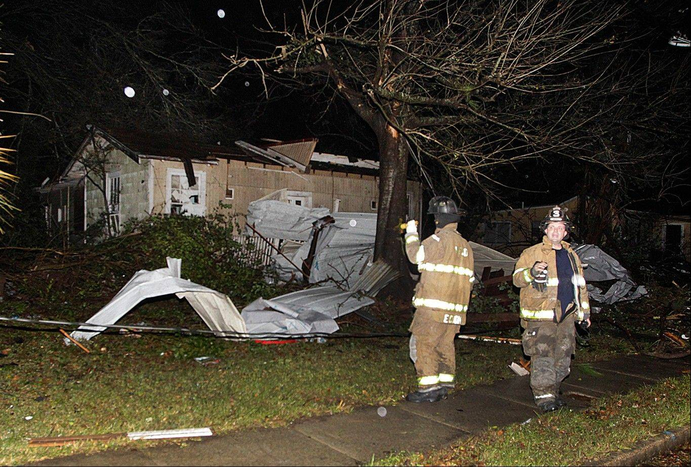 Firefighters go door-to-door on North Carlen Street in the Midtown section of Mobile, Ala. after a tornado touched down Tuesday, Dec. 25, 2012. A Christmas Day twister outbreak left damage across the Deep South while holiday travelers in the nation's much colder midsection battled sometimes treacherous driving conditions from freezing rain and blizzard conditions.