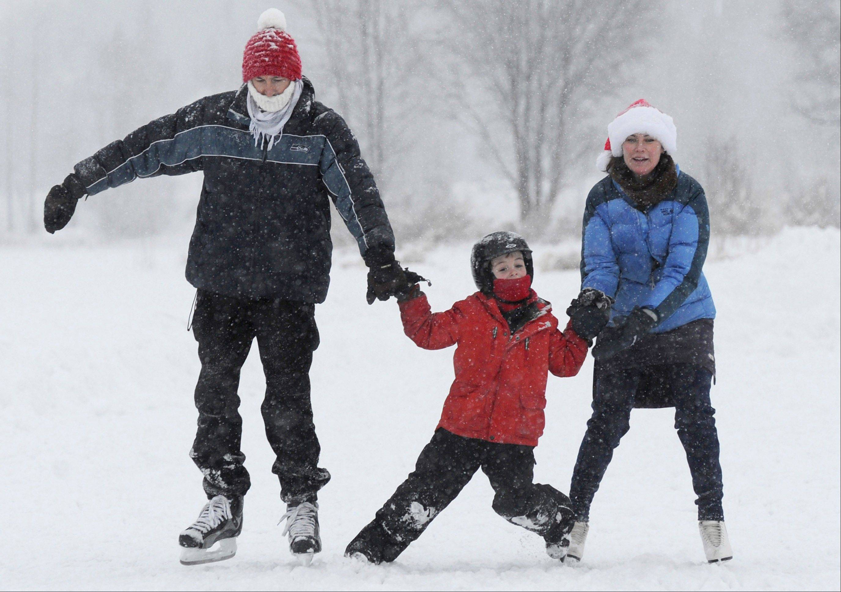 Kris Jones and his wife Robin Grendahl hang on to their son Erik Jones, 7, while ice skating at Westchester Lagoon in Anchorage during a snowstorm on Christmas Day, Tuesday, Dec. 25, 2012.