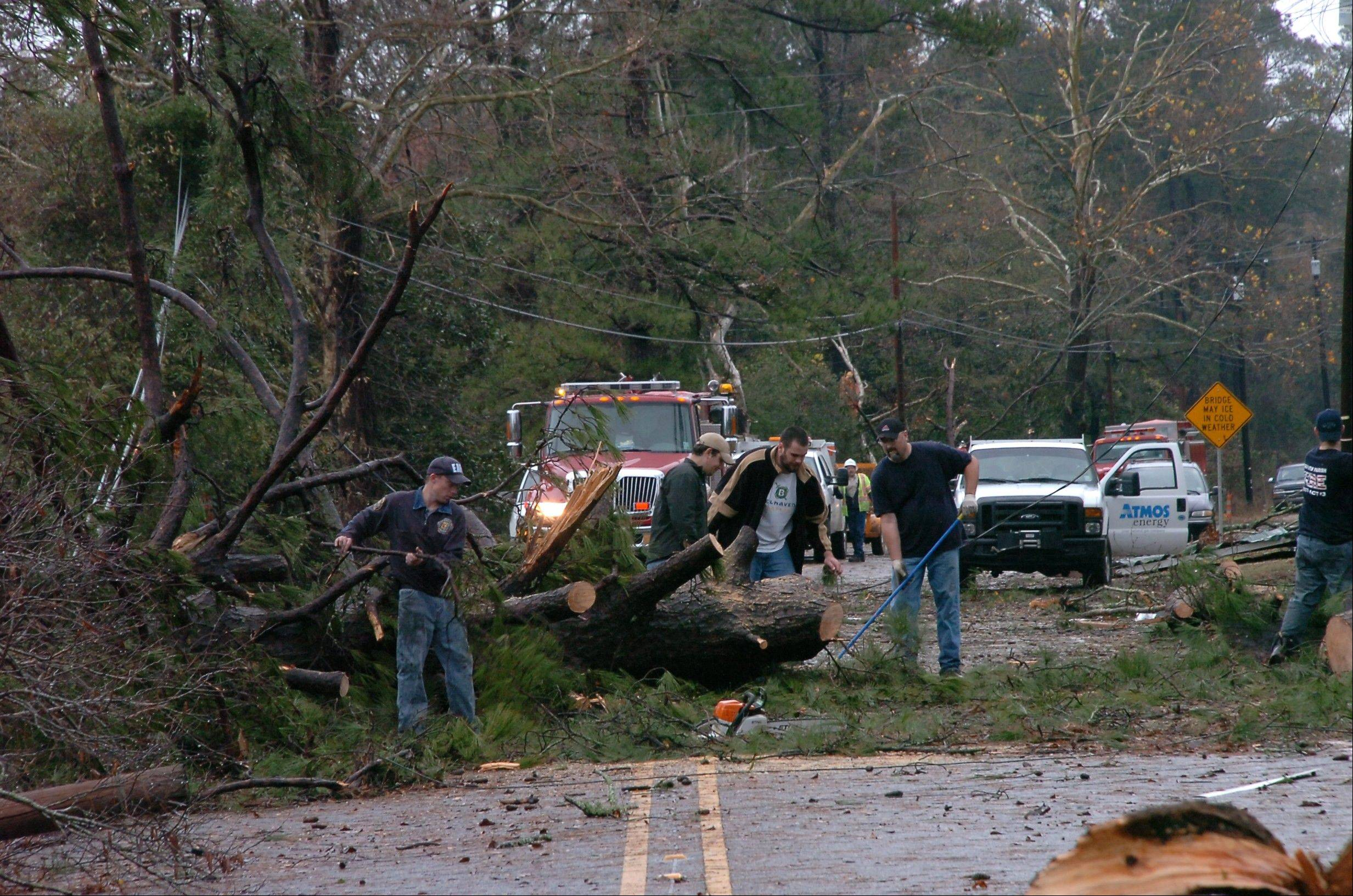 Members of the Alpine Volunteer Fire Department and the VA Fire Department clear debris from U.S. 71 in the Tioga, La. area, after an apparent tornado tore through the area Tuesday, Dec. 25, 2012.