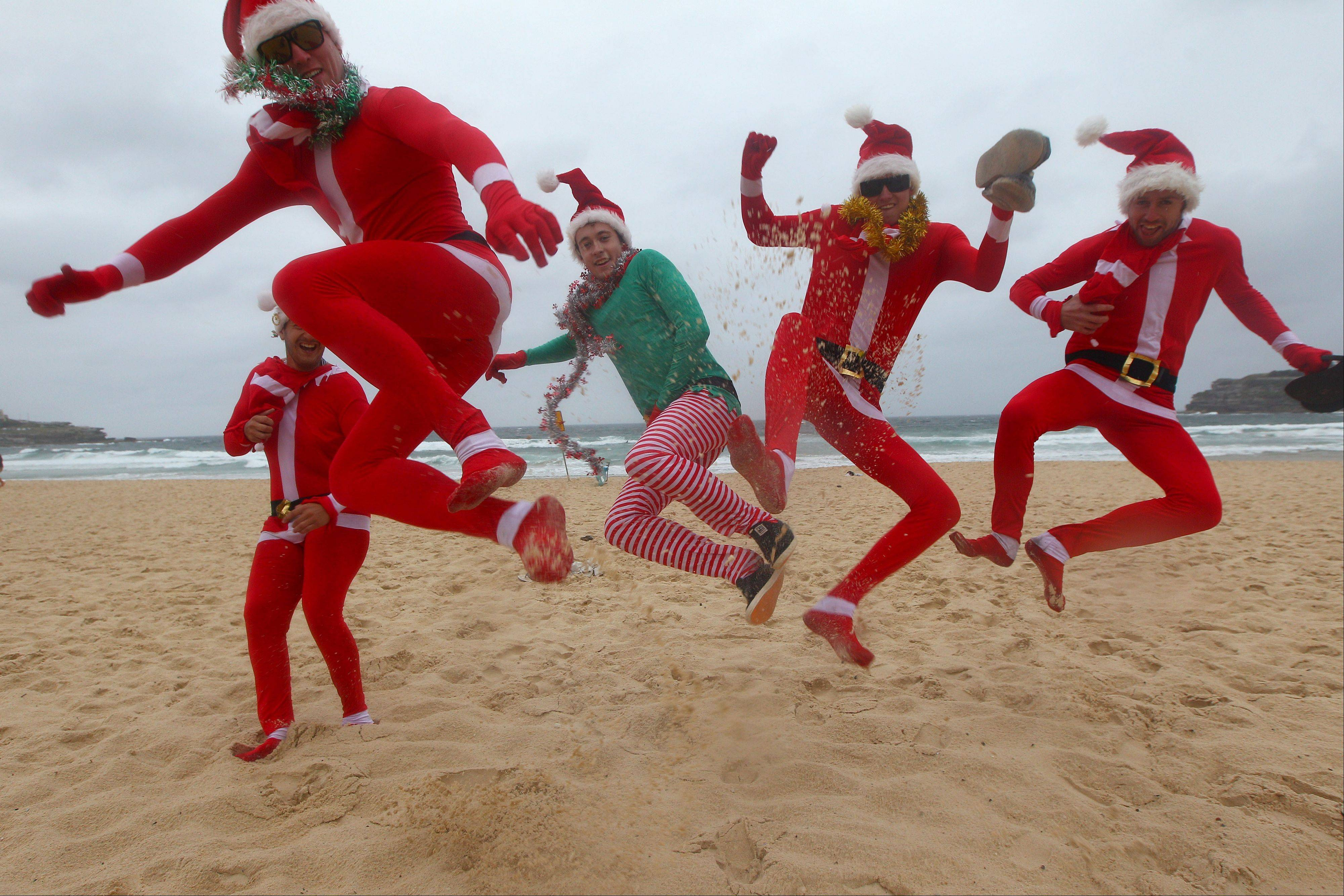 British travelers, left to right, Liam Skalley, John Arthurs, Ben Saunders, Sam Hope and Liam Fillingham kick up their heels as they celebrate Christmas Day despite wet and cold weather at Bondi Beach in Sydney, Australia, Tuesday, Dec. 25, 2012.
