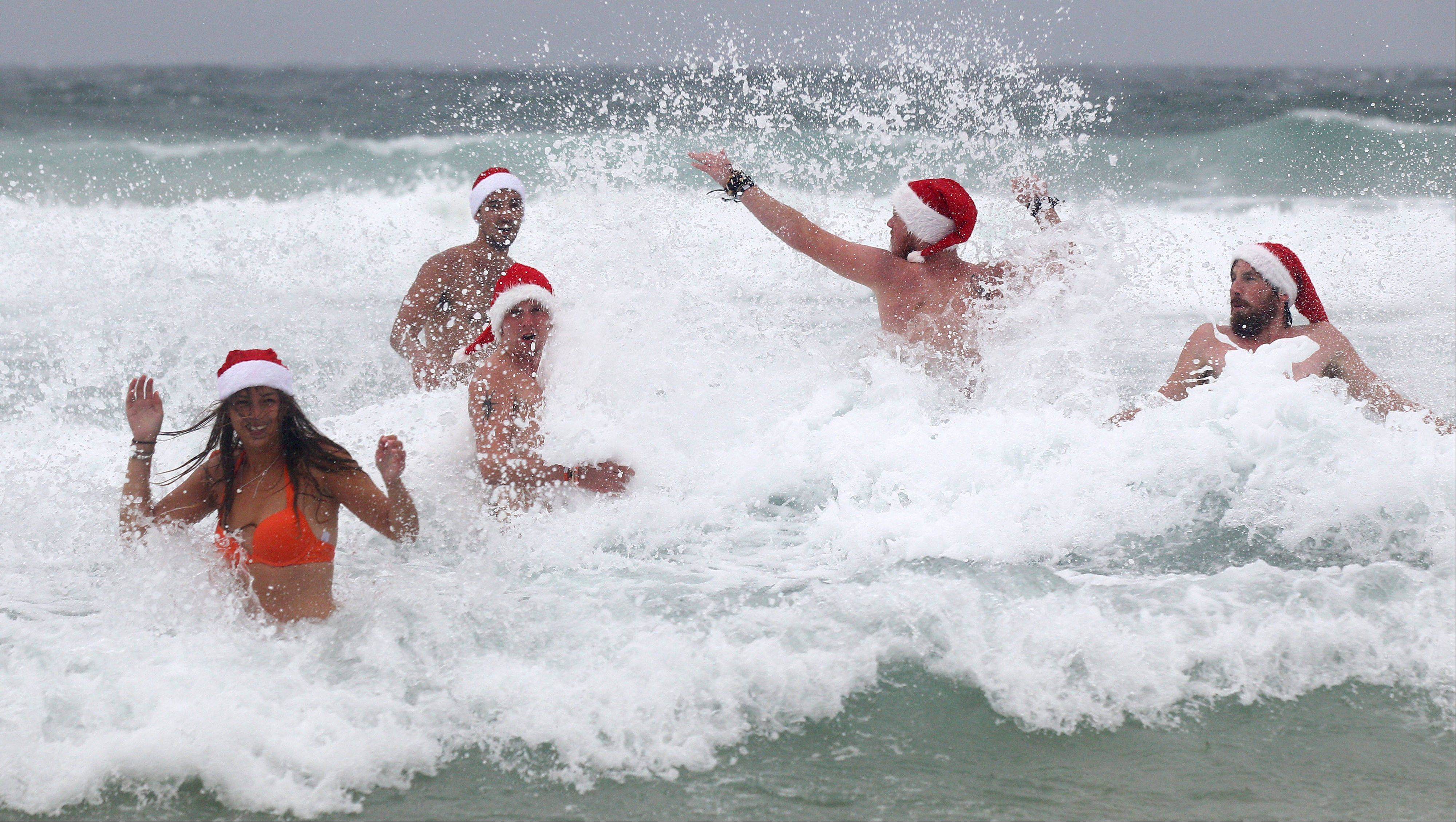British travelers, left to right, Isolde Lewis, Spencer Sullivan, Damon Hull, Lewis Conlon and Daniel Strange celebrate Christmas Day despite wet and cold weather at Bondi Beach in Sydney, Australia, Tuesday, Dec. 25, 2012.
