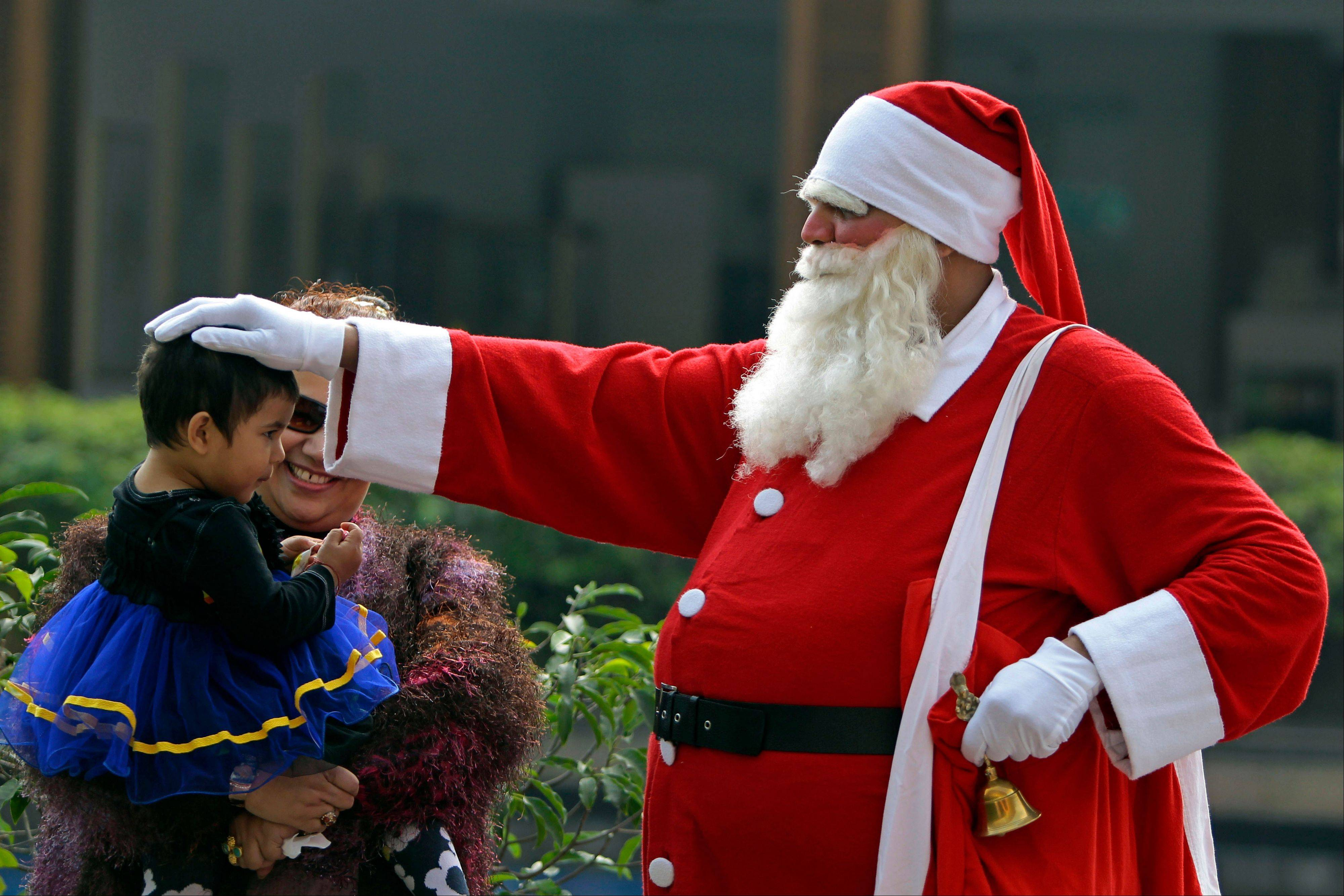 A man dressed as Santa Claus blesses a child at a Christmas Day party in Dhaka, Bangladesh, Tuesday, Dec. 25, 2012.