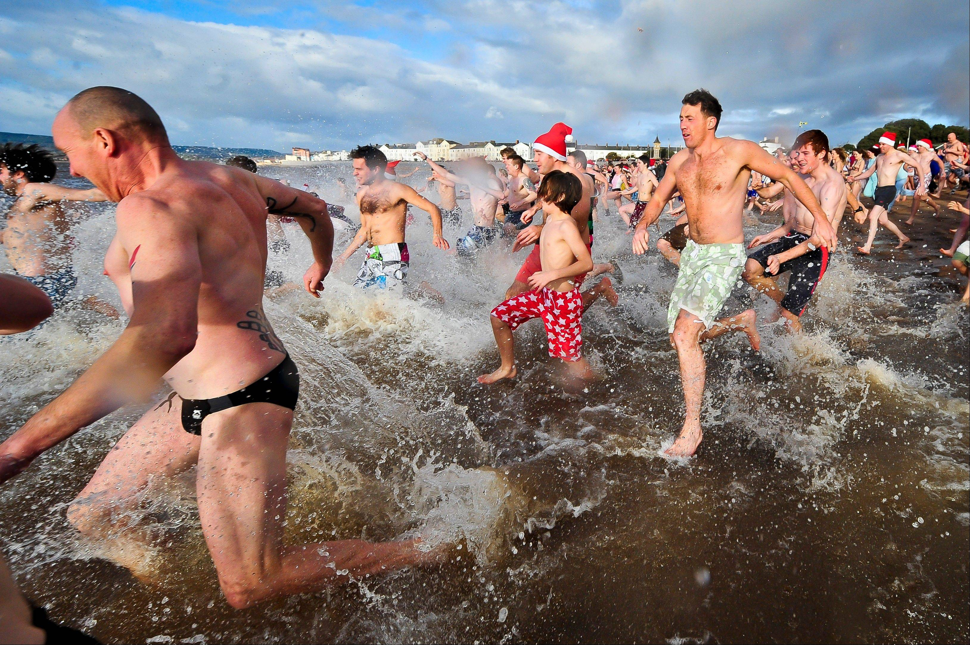 Swimmers take to the sea at Exmouth, south western England, for the annual Christmas Day swim, Tuesday Dec. 25, 2012.