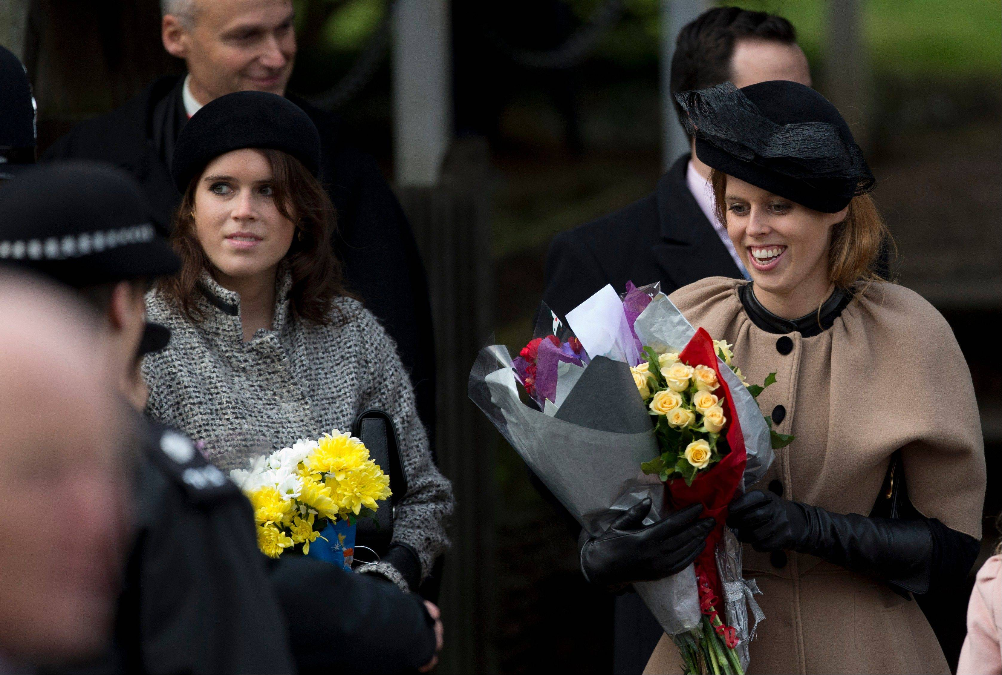 Britain's Queen Elizabeth II's granddaughters Princesses Beatrice, right, and Eugenie, left, hold flowers the Queen received from children after attending the British royal family's traditional Christmas Day church service in Sandringham, England, Tuesday, Dec. 25, 2012.