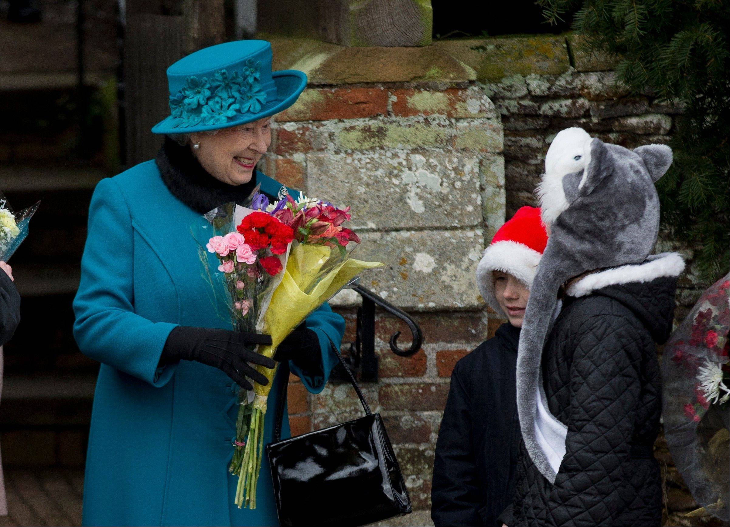 Britain's Queen Elizabeth II receives flowers from children after attending the British royal family's traditional Christmas Day church service in Sandringham, England, Tuesday, Dec. 25, 2012.