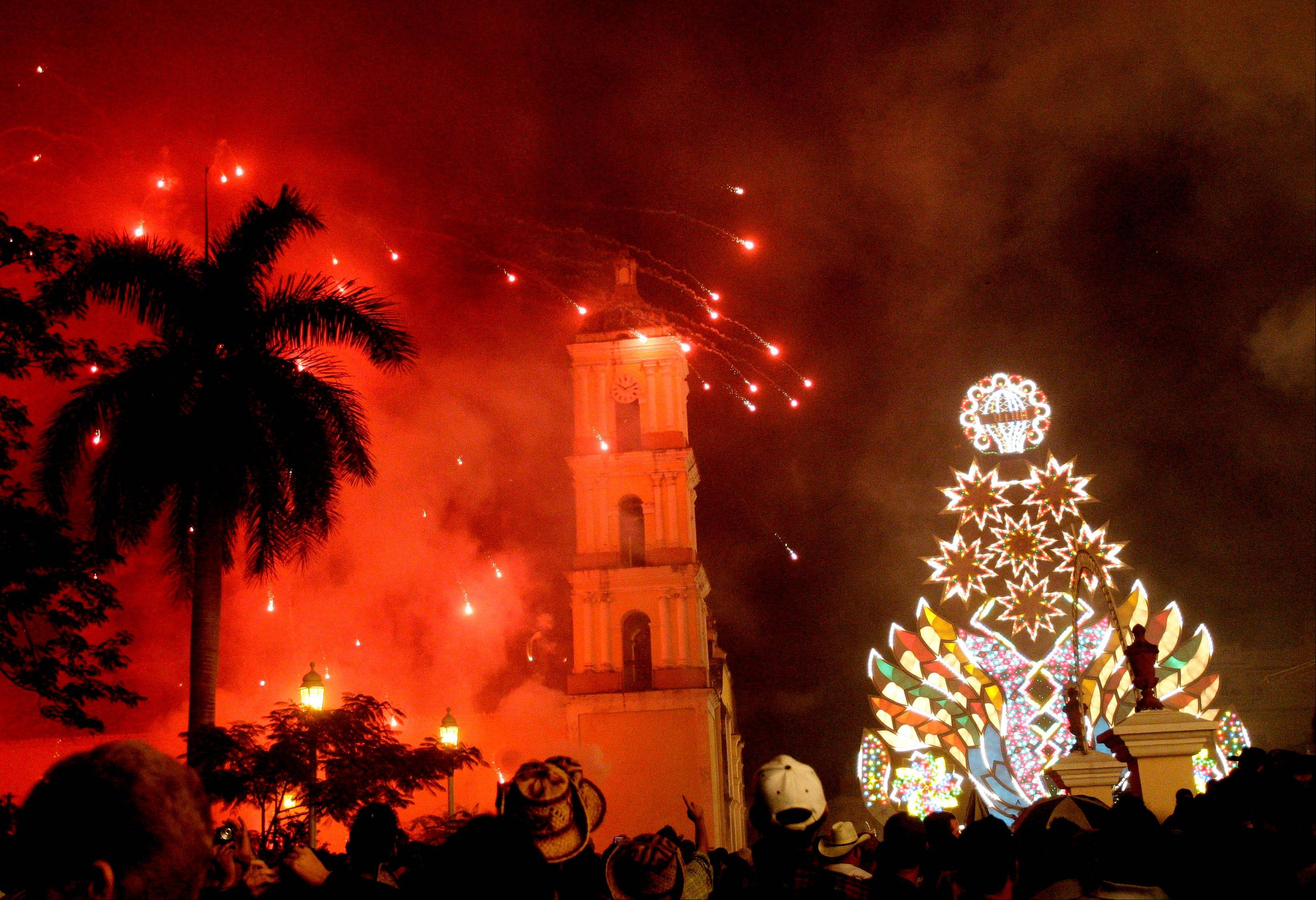 "Fireworks light up the church during a ""Parranda"" celebrating Christmas in the village of Remedios, Cuba, late Monday, Dec. 24, 2012. Remedios' parrandas evolved from a priest's attempt to attract residents to his Catholic church's Christmas Mass, and with time, it converted into the town's street party where residents compete in firework and Christmas displays."