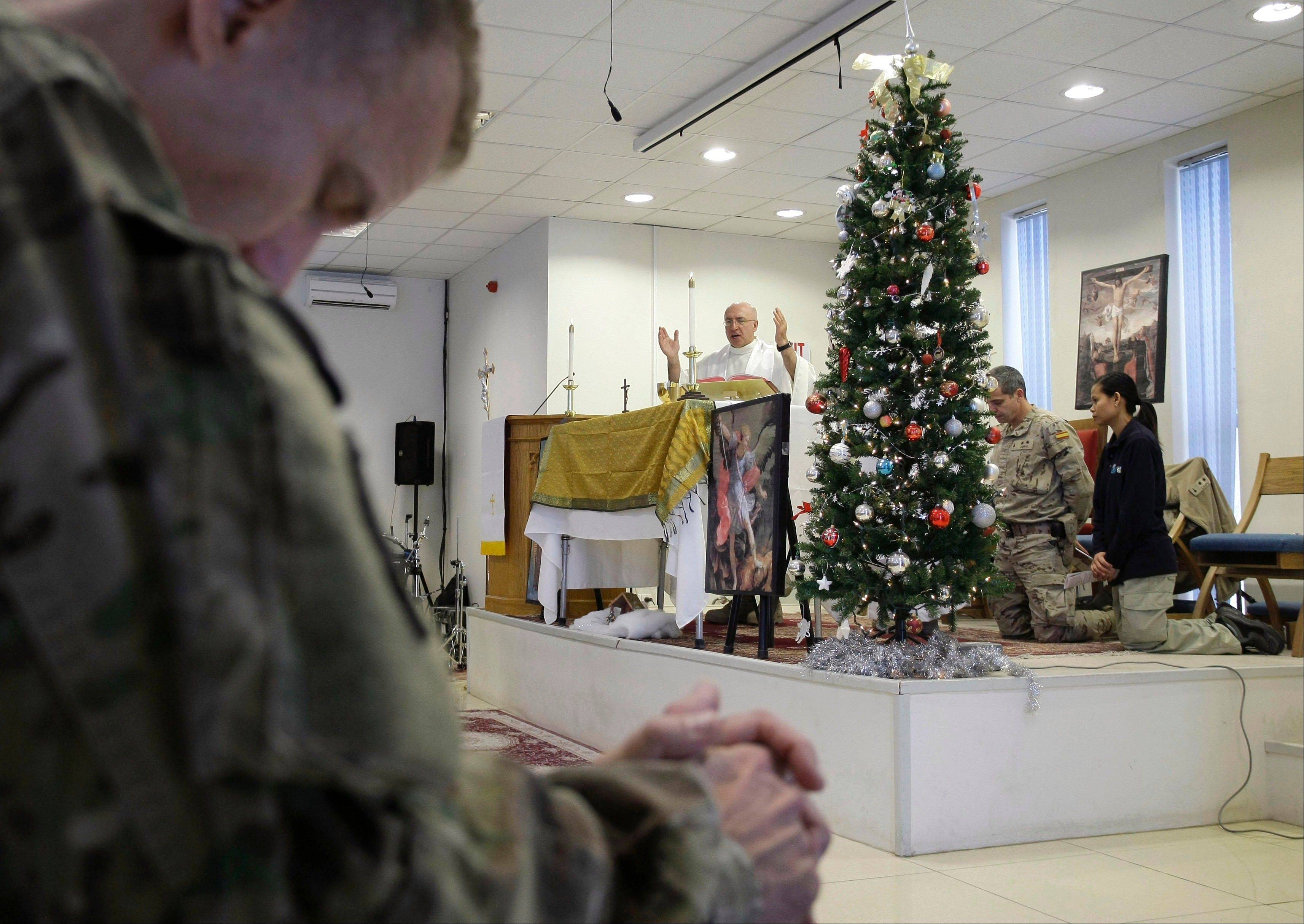 U.S. Army Chaplain Lt. Col. George Rzasowsk, center, leads a Christmas service for soldiers and service members with the NATO- led International Security Assistance Force (ISAF) at the U.S.-led coalition base in Kabul, Afghanistan, Tuesday, Dec. 25, 2012.
