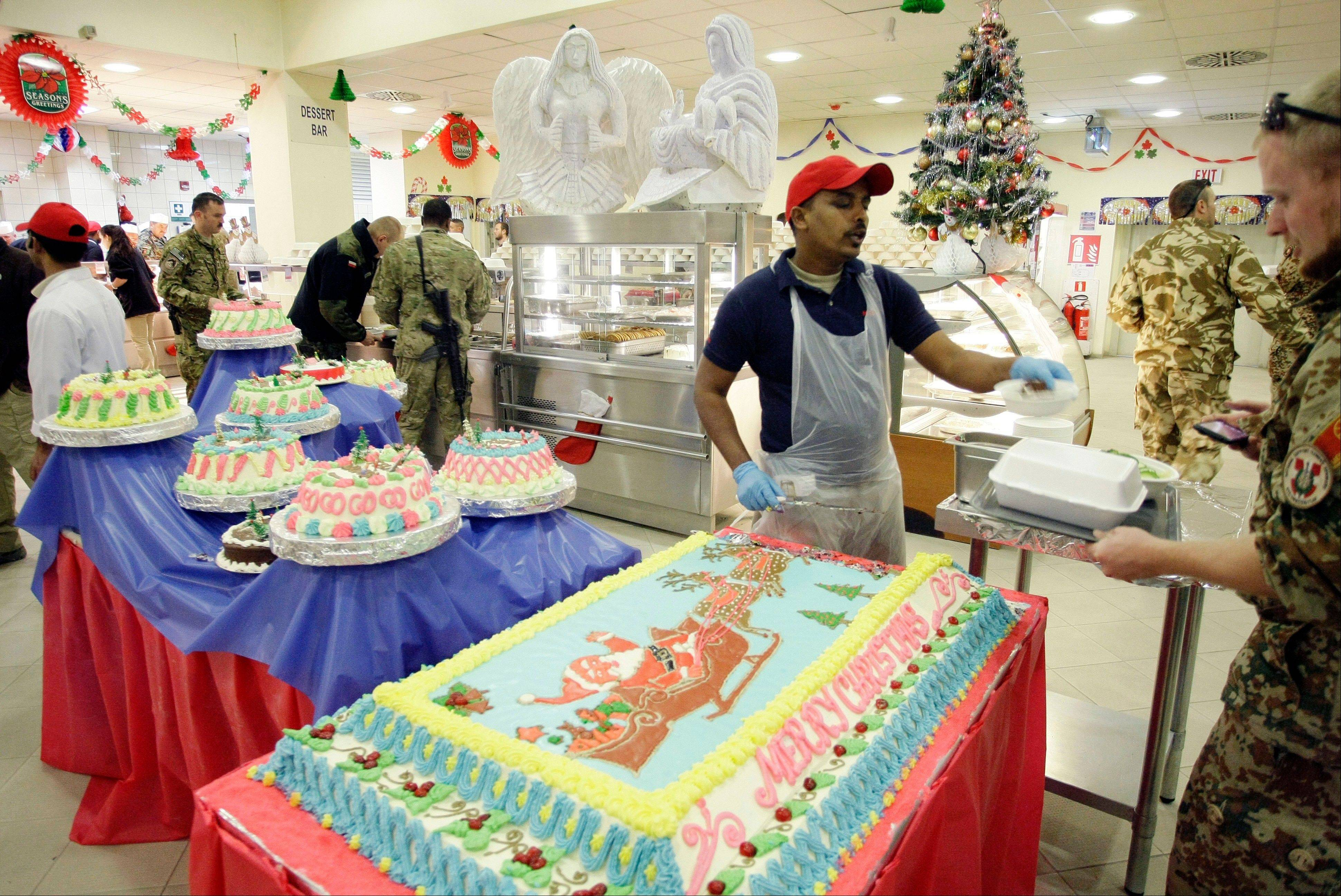 A worker, center, serves cake to a soldier with the NATO-led International Security Assistance Force (ISAF) during Christmas dinner at a dining facility at the U.S.-led coalition base in Kabul, Afghanistan, Tuesday, Dec. 25, 2012.