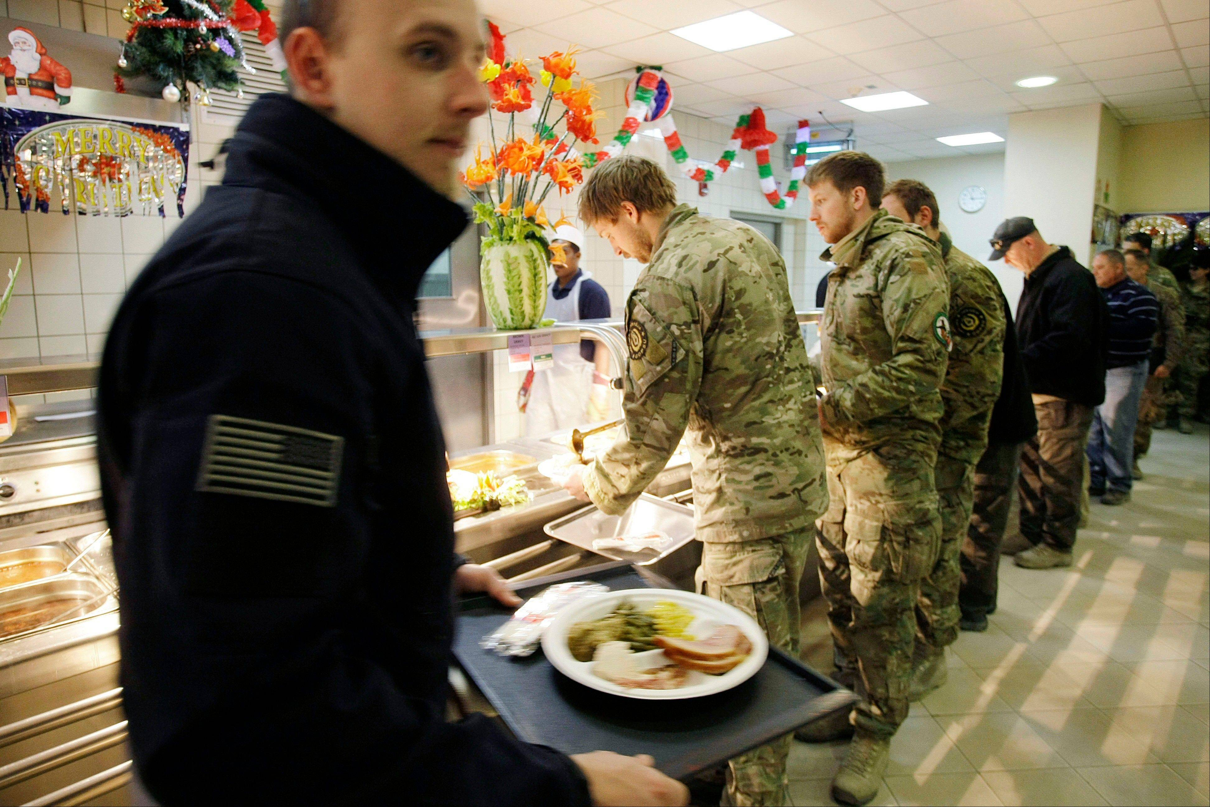 Soldiers and service members with the NATO-led International Security Assistance Force (ISAF) wait to be served Christmas dinner at a dining facility at the U.S.-led coalition base in Kabul, Afghanistan, Tuesday, Dec. 25, 2012.