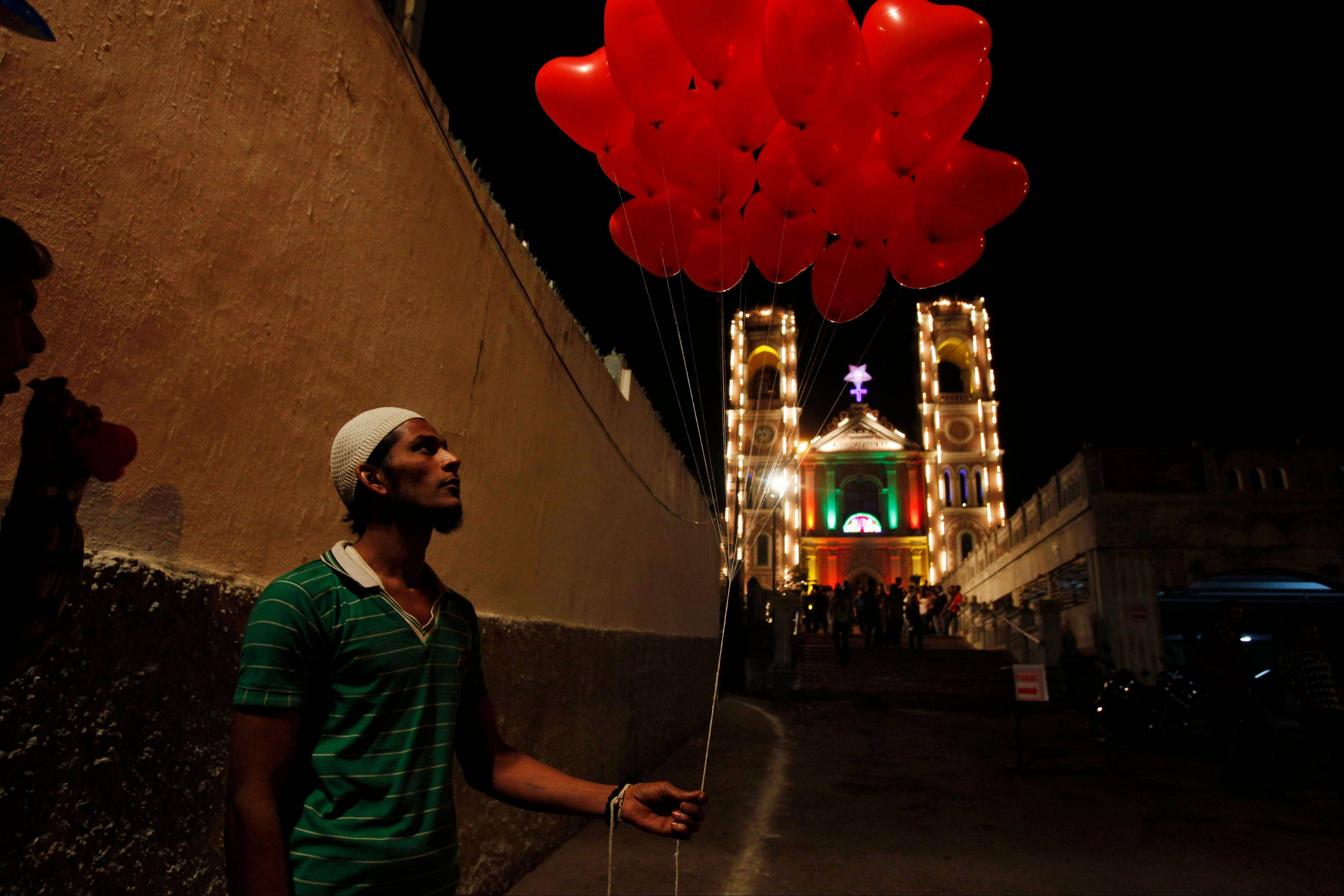 An Indian Muslim vendor sells balloons in front of St Joseph Cathedral during Christmas celebrations in Hyderabad, India, early Tuesday, Dec. 25, 2012. Although Christians comprise only two percent of the population Christmas is a national holiday and is observed across the country as an occasion to celebrate.
