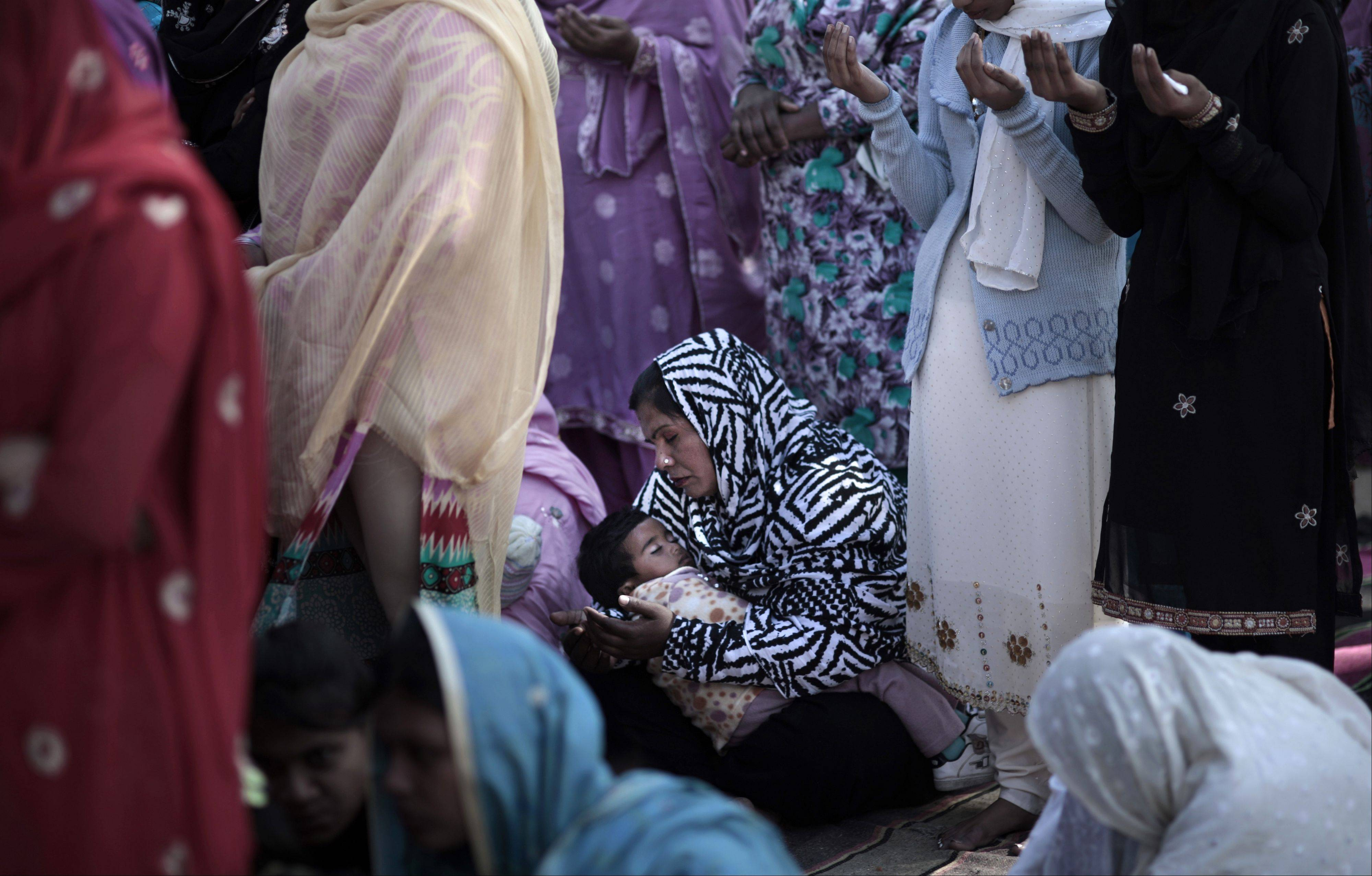 A Pakistani child, center, sleeps on her mother's lap, while she and other women pray during an outdoor Mass on Christmas Day, in a Christian neighborhood in Islamabad, Pakistan, Tuesday, Dec. 25, 2012.