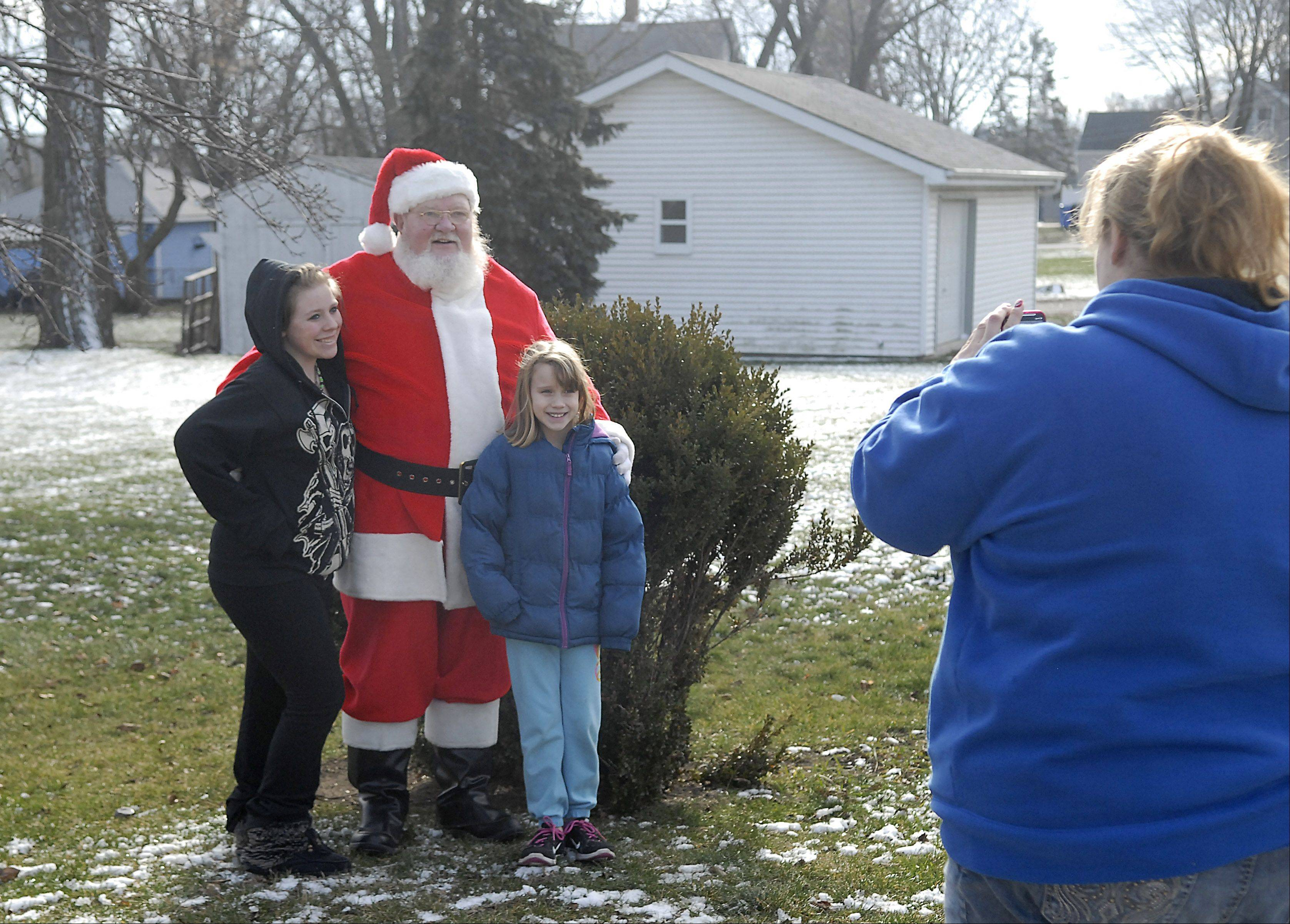 Nichole Gibson of South Elgin takes a photo of her daughters Alyssa Goerr, 16, and Danielle Gibson, 9, with Richard Ahrens of East Dundee in South Elgin yesterday. The empty lot behind them is where Ahrens former home once stood, and is where his tradition of dressing up as Santa for fun started over 20 years ago. Even though he moved to East Dundee about eight years ago, he still comes back to the same corner for a few hours every Christmas Day.