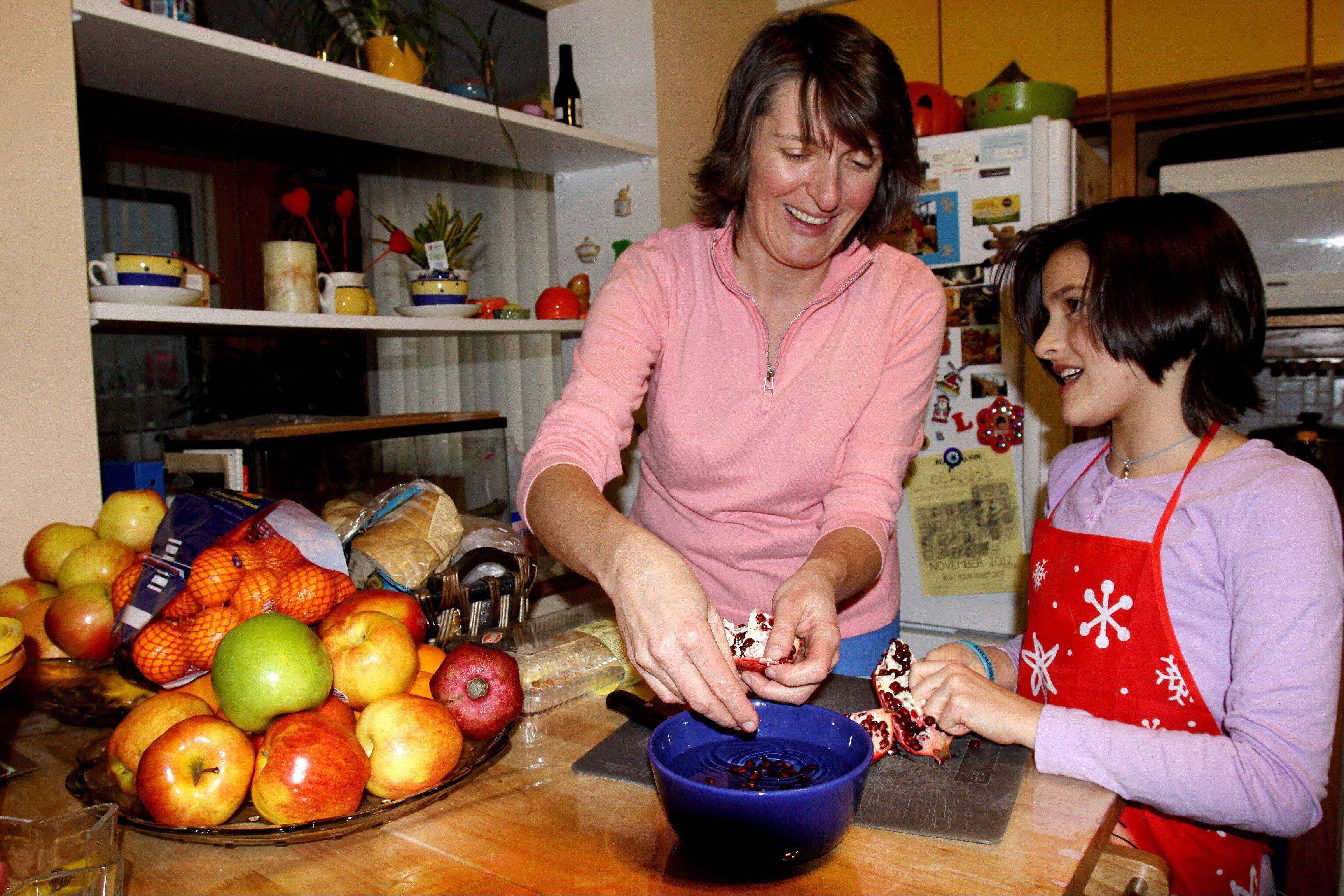 Monika Moro of Lombard helps her 10-year-old daughter, Alison, cut a pomegranate for an afternoon snack.