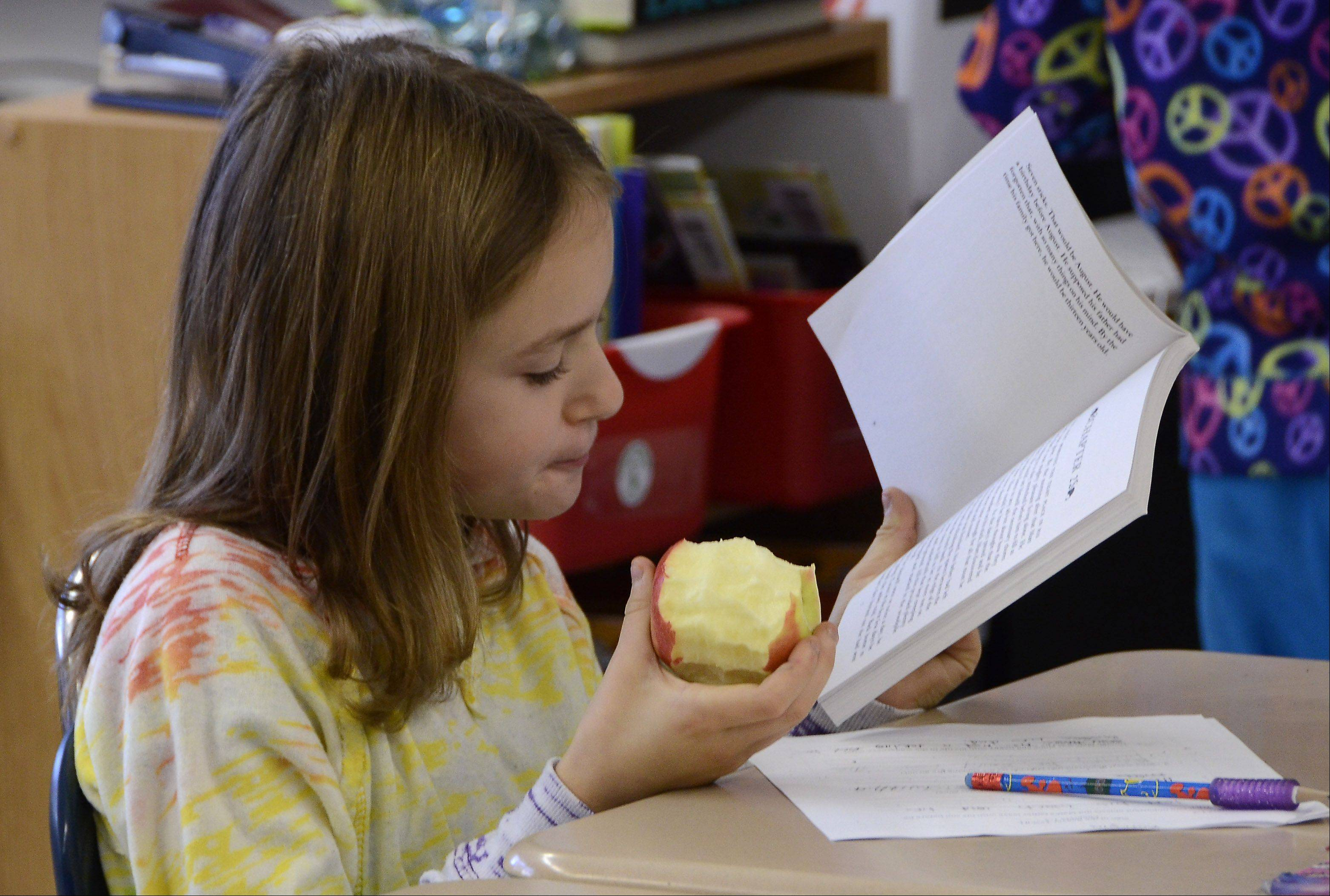 Kotryna Povilanskas snacks on an apple during a midmorning class at Windsor Elementary School in Arlington Heights.