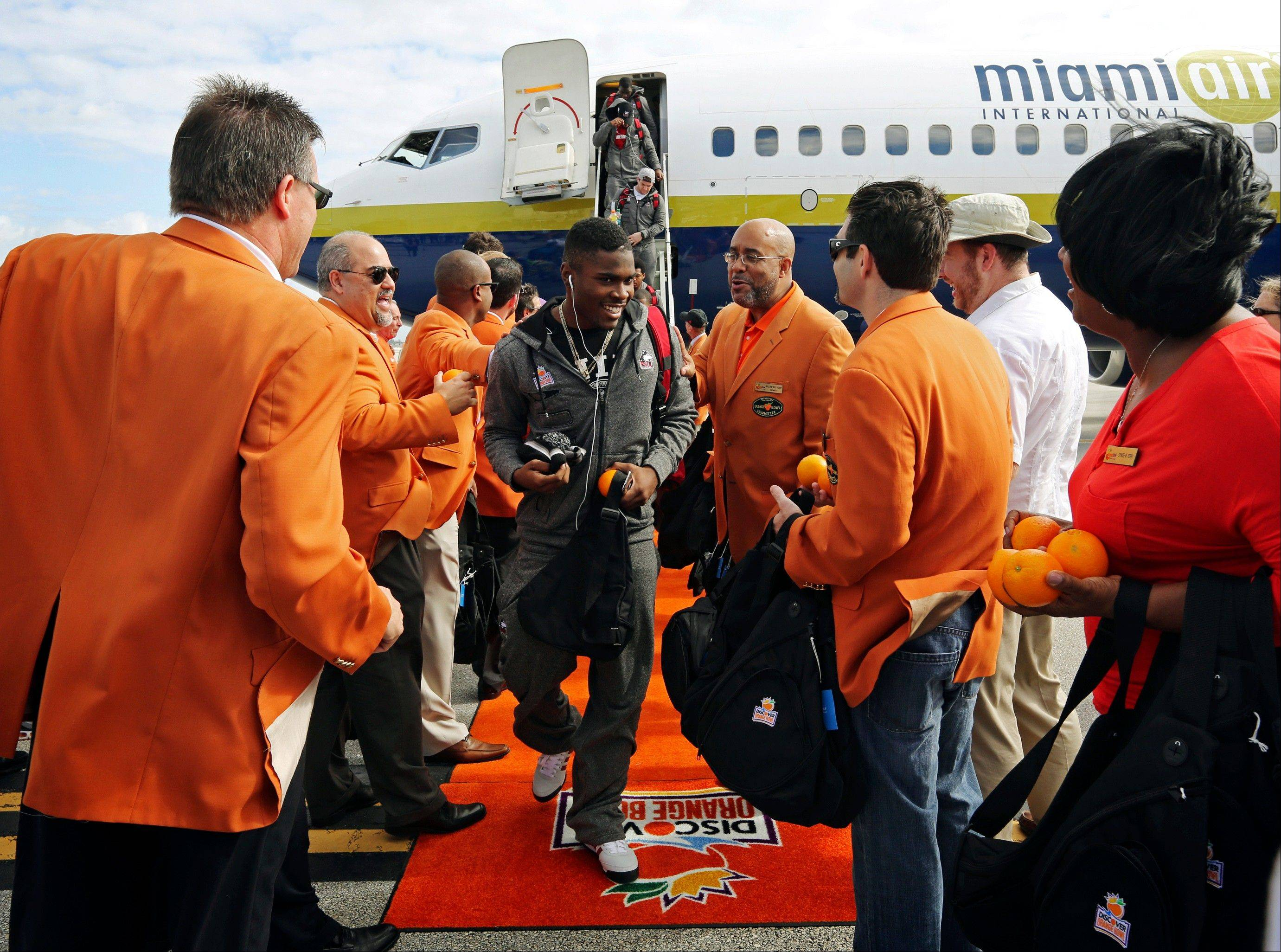 Northern Illinois players are greeted Wednesday by Orange Bowl Committee Members handing out oranges and gift bags as the team arrives at Miami International Airport.