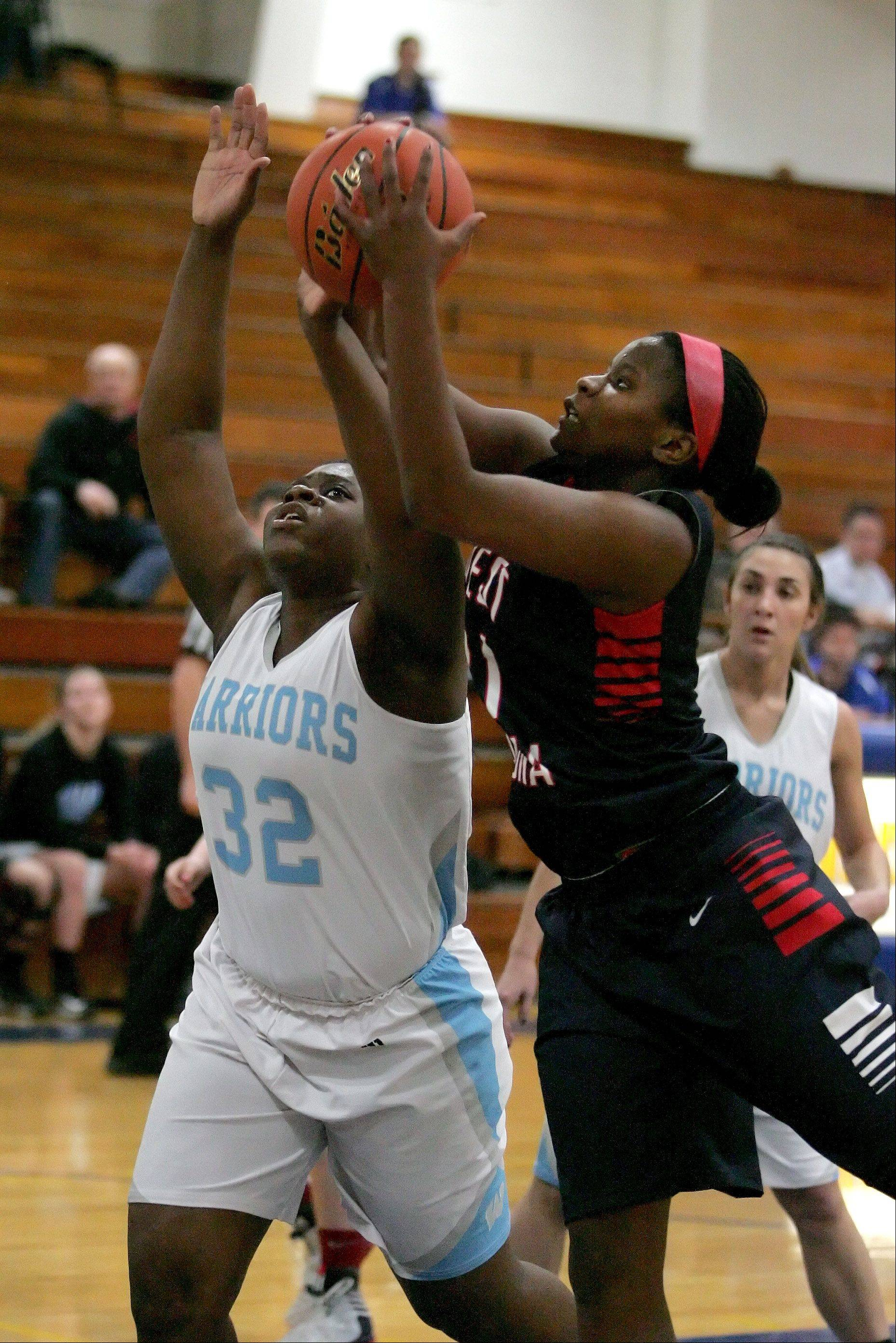 Emma Udota of Willowbrook, left and Elizabeth Skaggs, right, of West Aurora go up for a rebound in girls basketball action at the 2012 Bill Neibch Holiday Tournament at Wheaton North High School on Wednesday.
