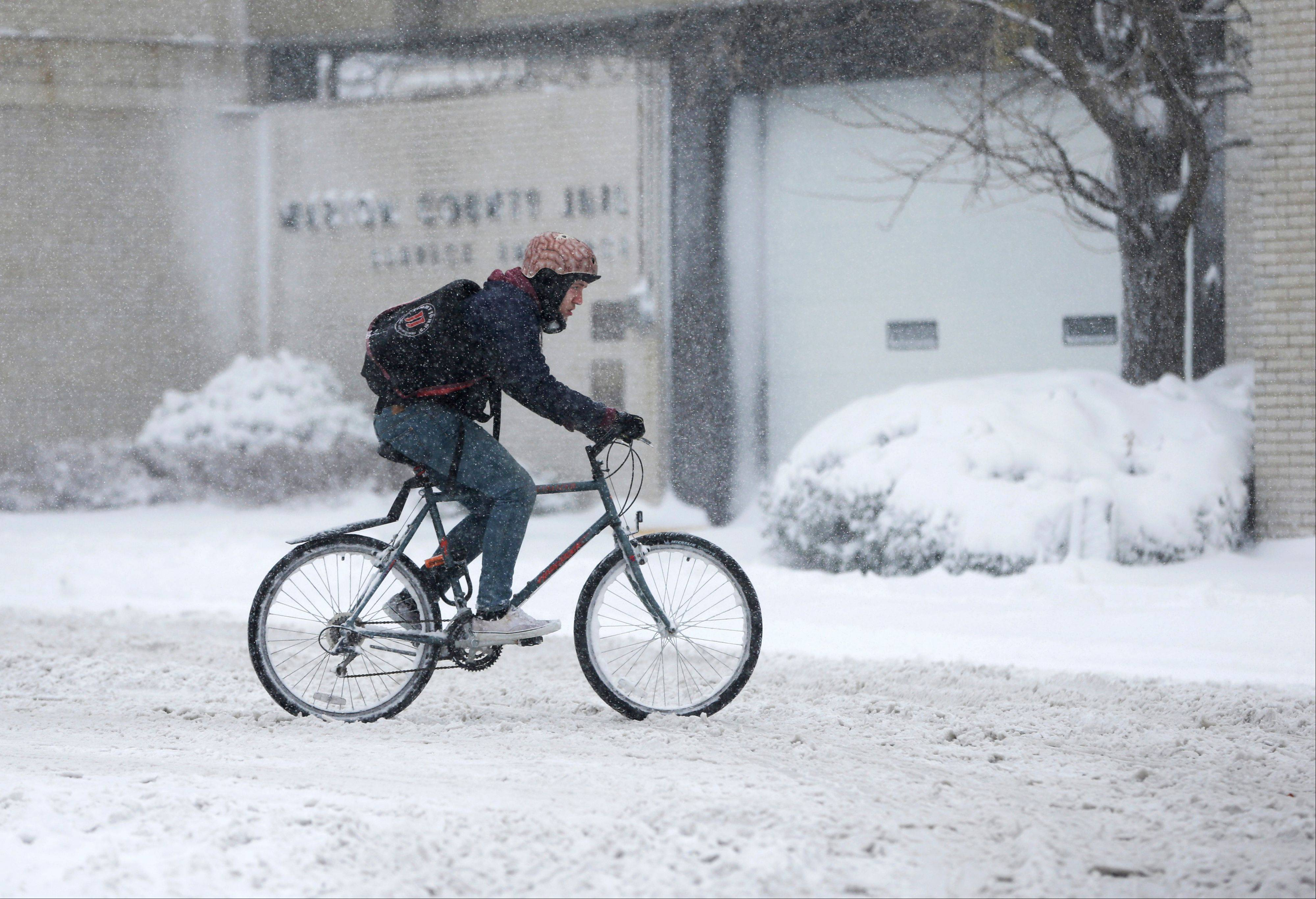 A man rides his bicycle through the streets as he makes a delivery Wednesday in Indianapolis. The blizzard warning issued the day before by National Weather Service came to fruition in the region as winds picked up and snow began falling in earnest. The Pacers postponed their game with the Chicago Bulls on Wednesday night.