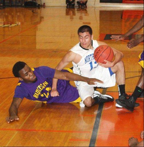 St. Charles North�s Tony Neari battles Waukegan�s Quintin Davis for a loose ball Thursday at the Pontiac Holiday Tournament.