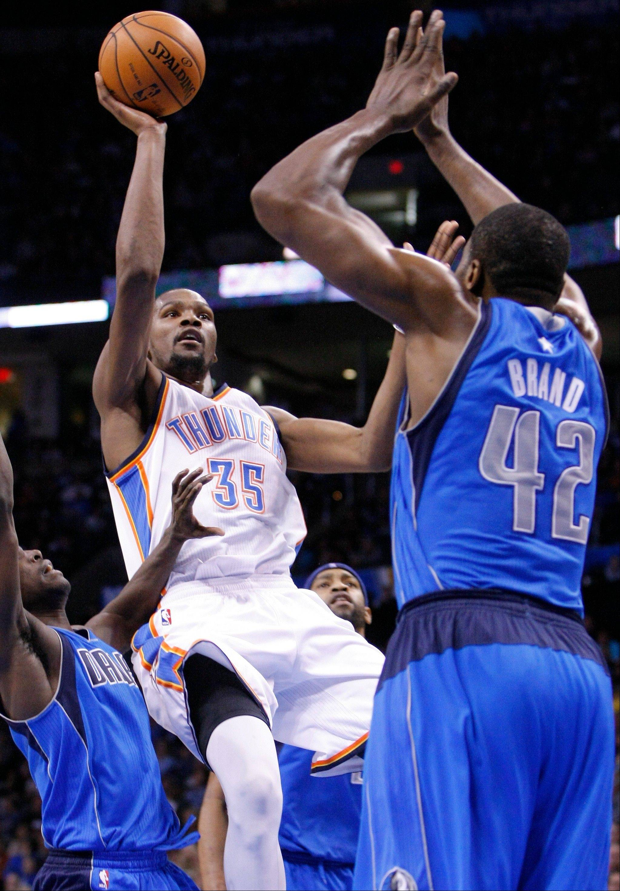 Thunder forward Kevin Durant, center, goes up for a basket in front of the Dallas Mavericks� Elton Brand during the second half Thursday in Oklahoma City.