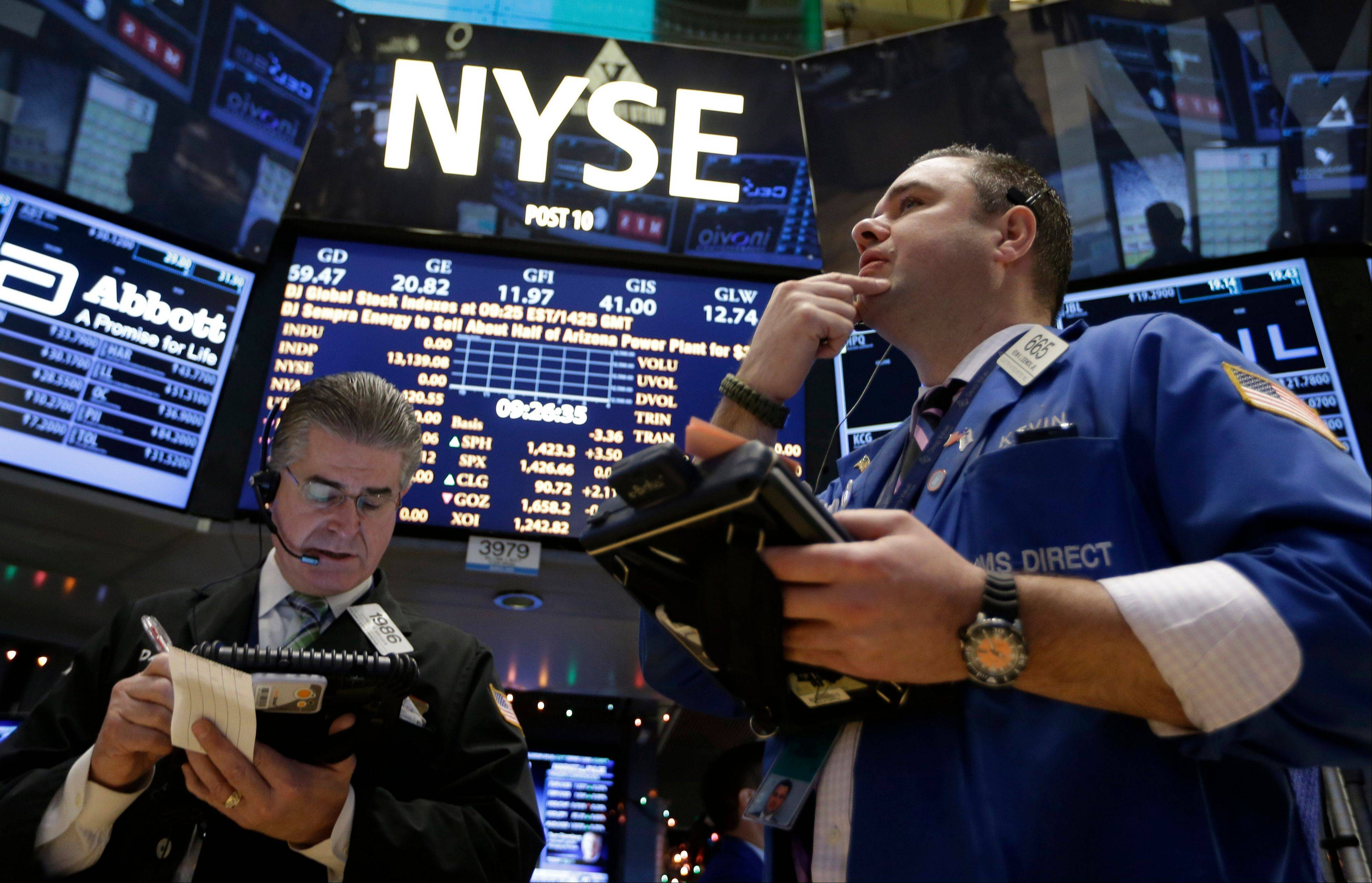 In this Wednesday, Dec. 26, 2012, photo, Daniel Kryger, left, and Kevin Lodewick Jr., right, work on the floor of the New York Stock Exchange in New York. Stocks are edging higher on Thursday as hopes dim that a budget deal will be reached before a deadline at the end of the year.