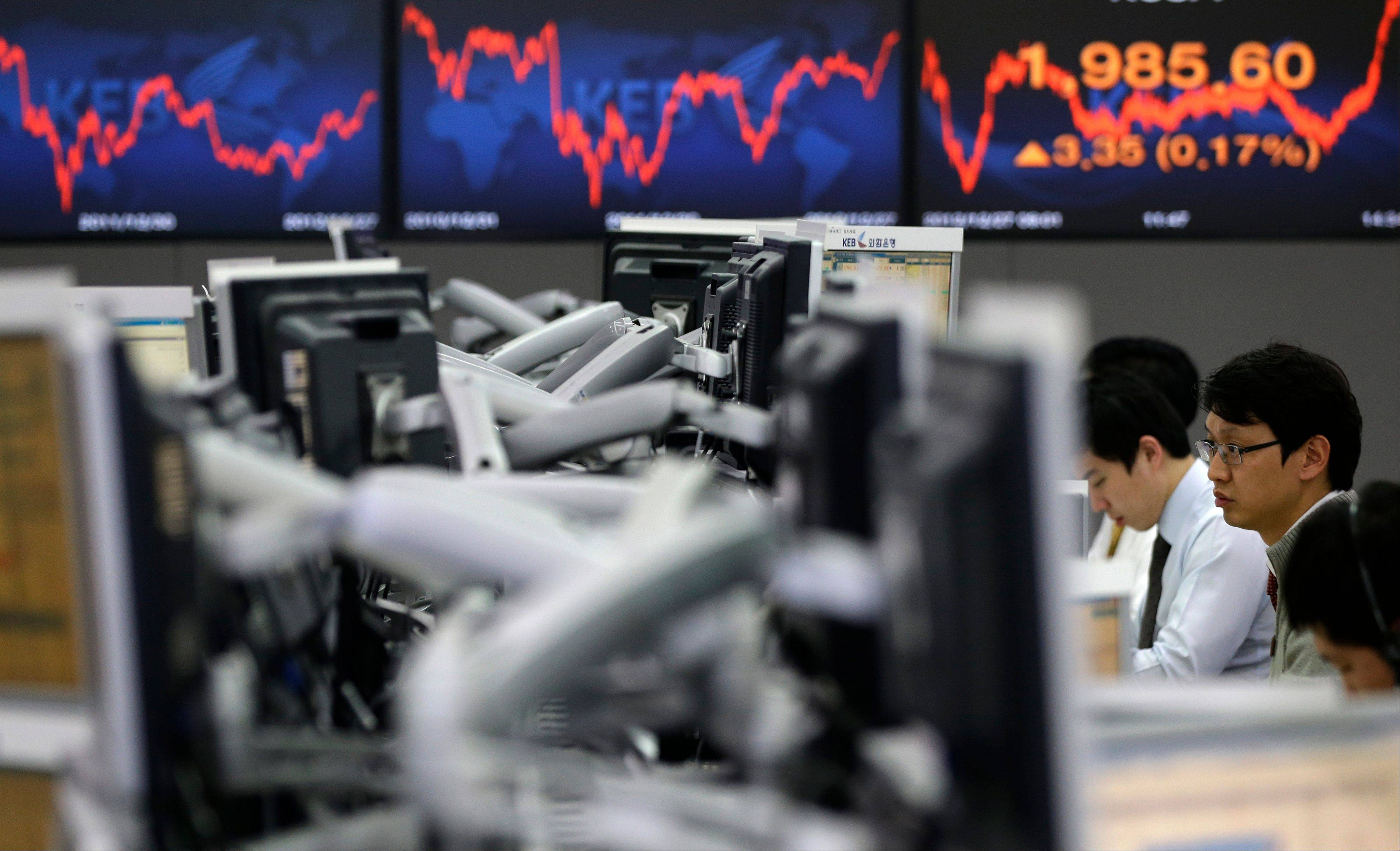 A currency trader looks at the computer monitors near a screen showing the Korea Composite Stock Price Index (KOSPI), right, at the foreign exchange dealing room of the Korea Exchange Bank headquarters in Seoul, South Korea, Thursday, Dec. 27, 2012. Most of Asian markets rose Thursday on optimism a new Japanese government will stimulate its sluggish economy.