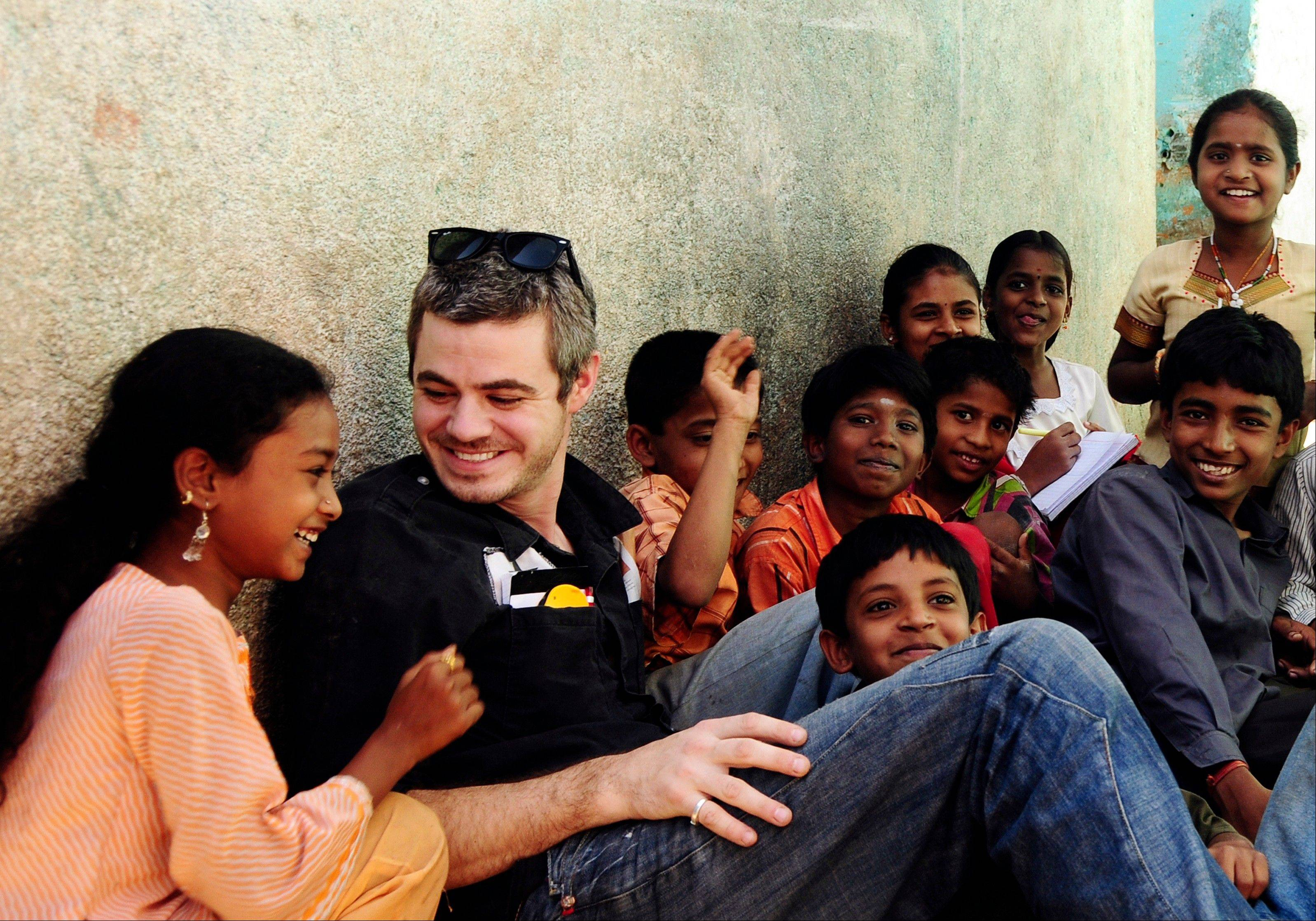 Scott Harrison talks with school children as he visits a school water project in India. His organization has funded nearly 7,000 clean water projects in some of the poorest areas of the world.