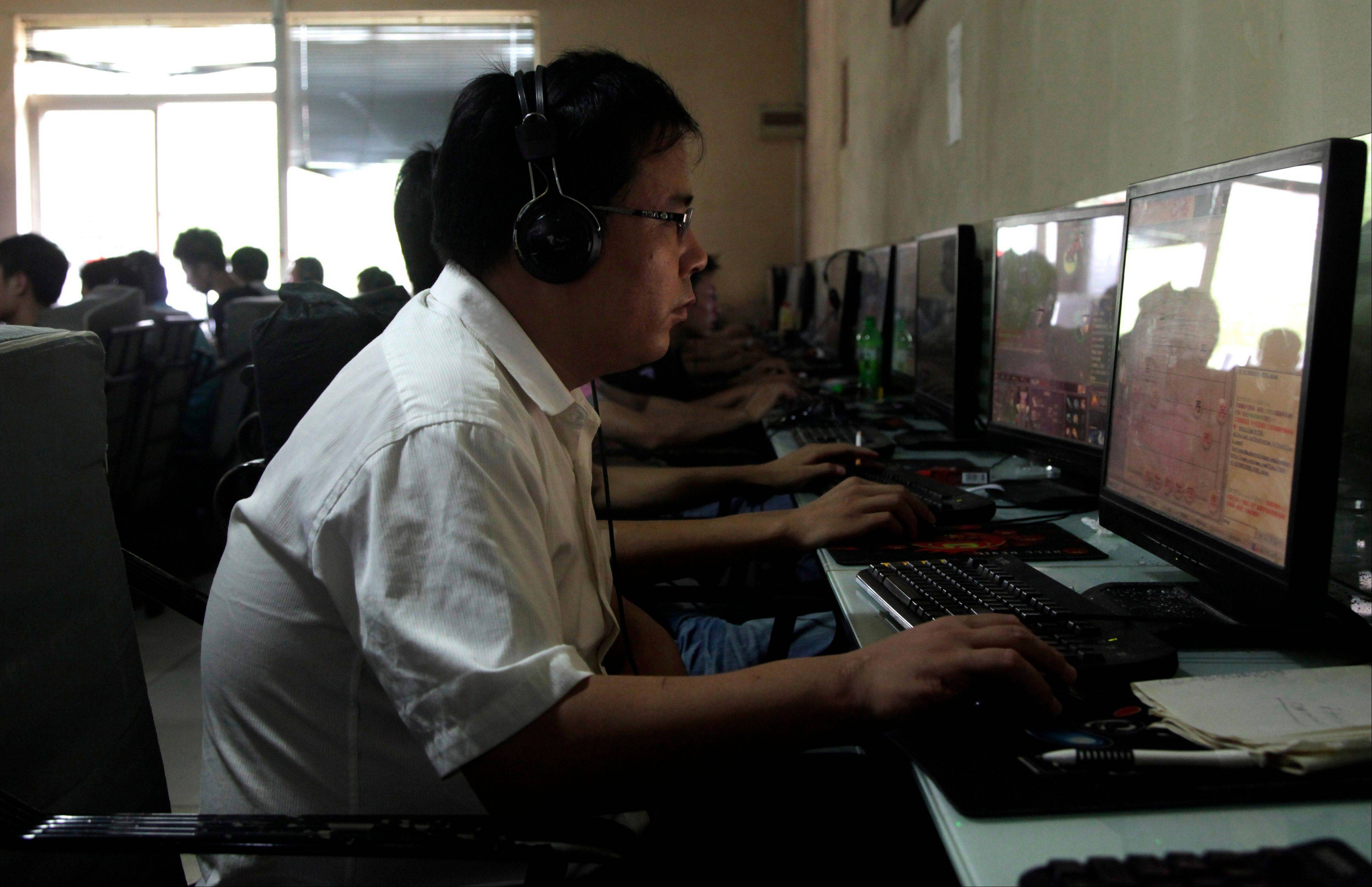 A Chinese man uses a computer at an Internet cafe in Beijing. China's new communist leaders are increasing already tight controls on Internet use and electronic publishing following a spate of embarrassing online reports about official abuses.
