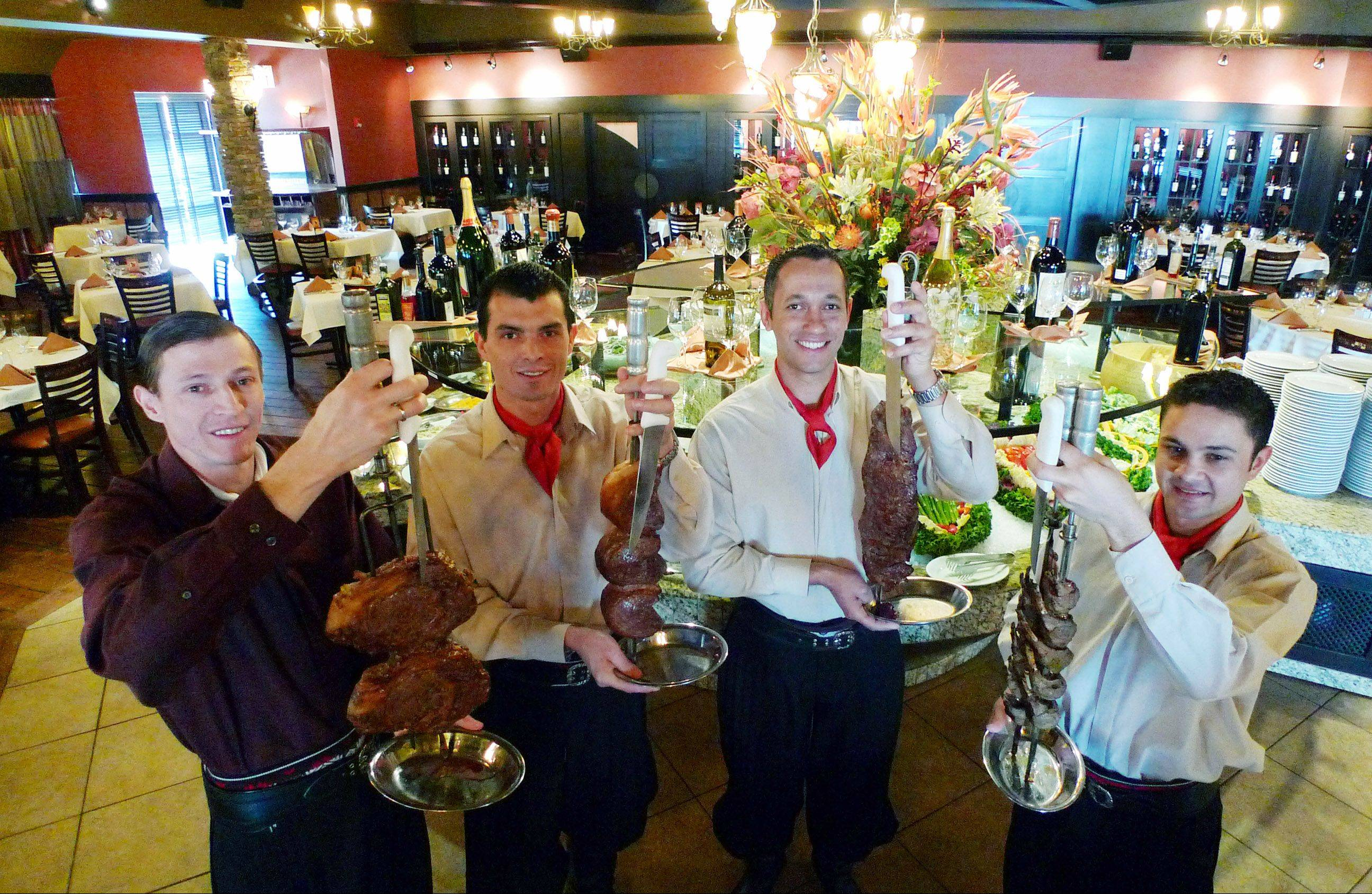 The gauchos at Chama Gaucha Brazilian Steakhouse in Downers Grove show off their signature skewered meats.