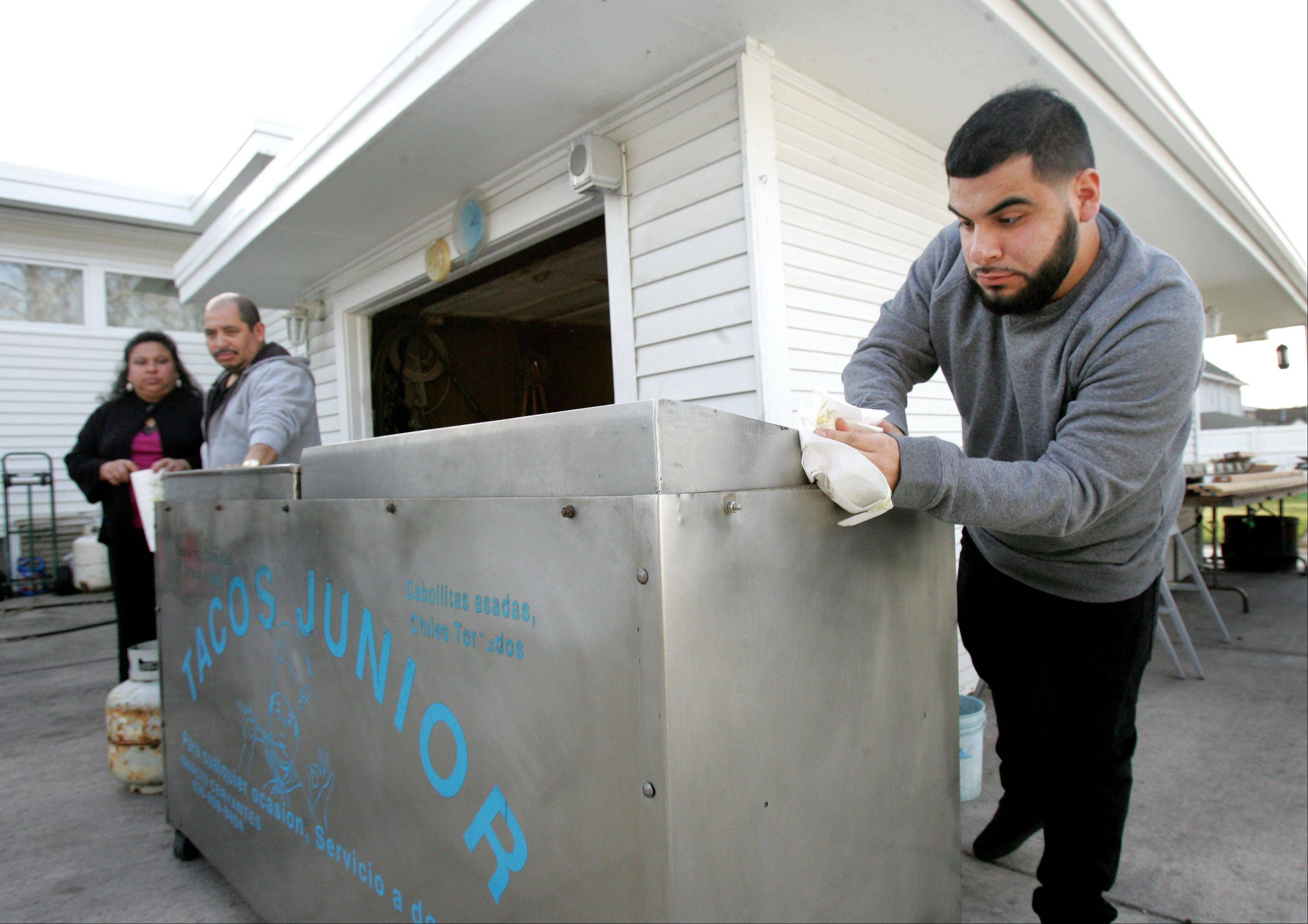 "Ignacio ""Nacho"" Cervantes Jr. cleans up a taco cart for Tacos Junior, the catering business owned by his family, as his parents look on at their Aurora home. In January, Ignacio will be recognized as one of the ""Phenomenal Men of the Year"" by the Aurora-based organization Boys II Men."