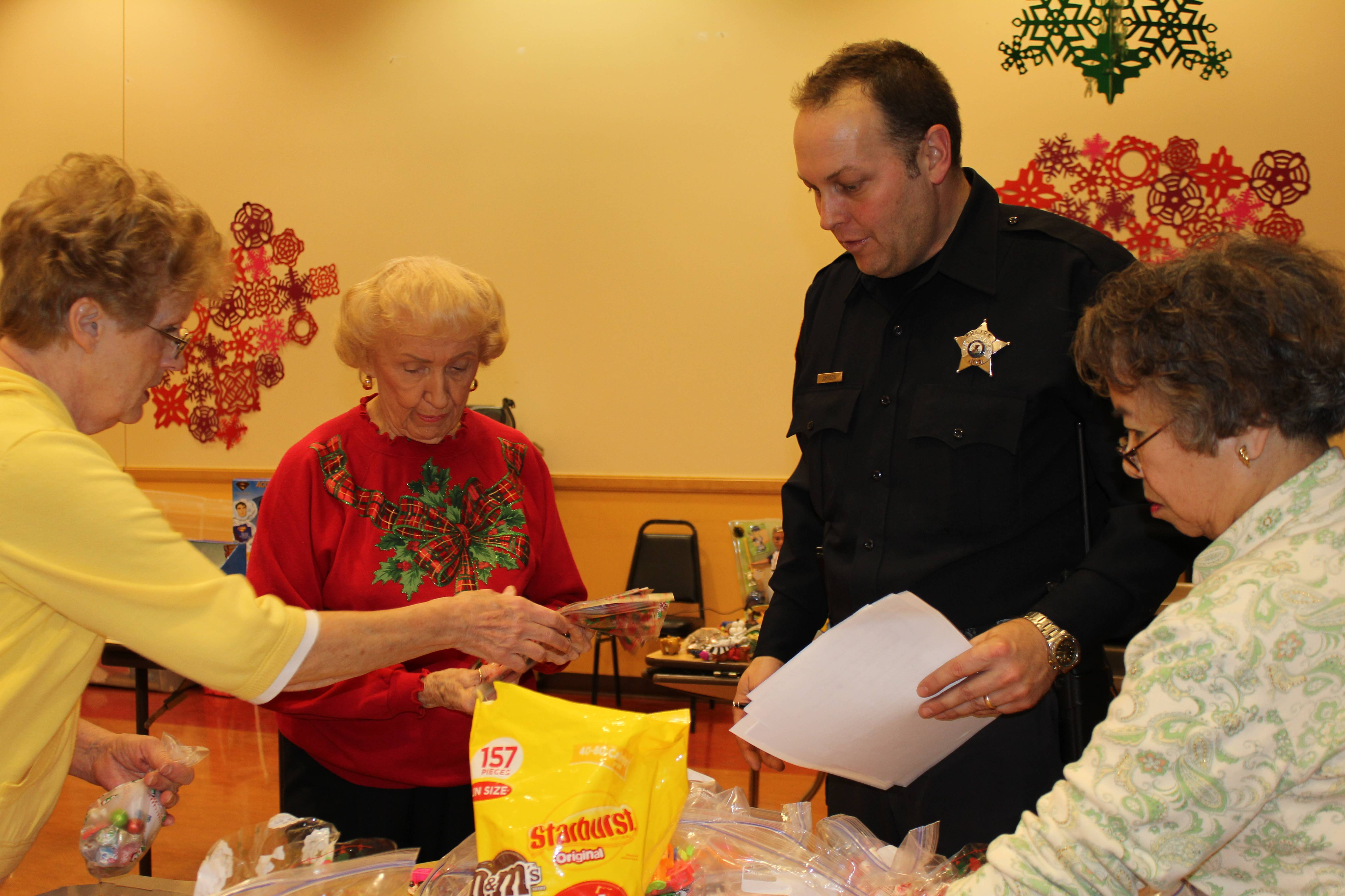 (pictured left to right) Volunteers Pat Miller and Helen Doney assist Des Plaines Police Officer Colin Johnson and volunteer Maria Lamblad at the wrapping party. (Not pictured Police Officer Michael Heidkamp.)